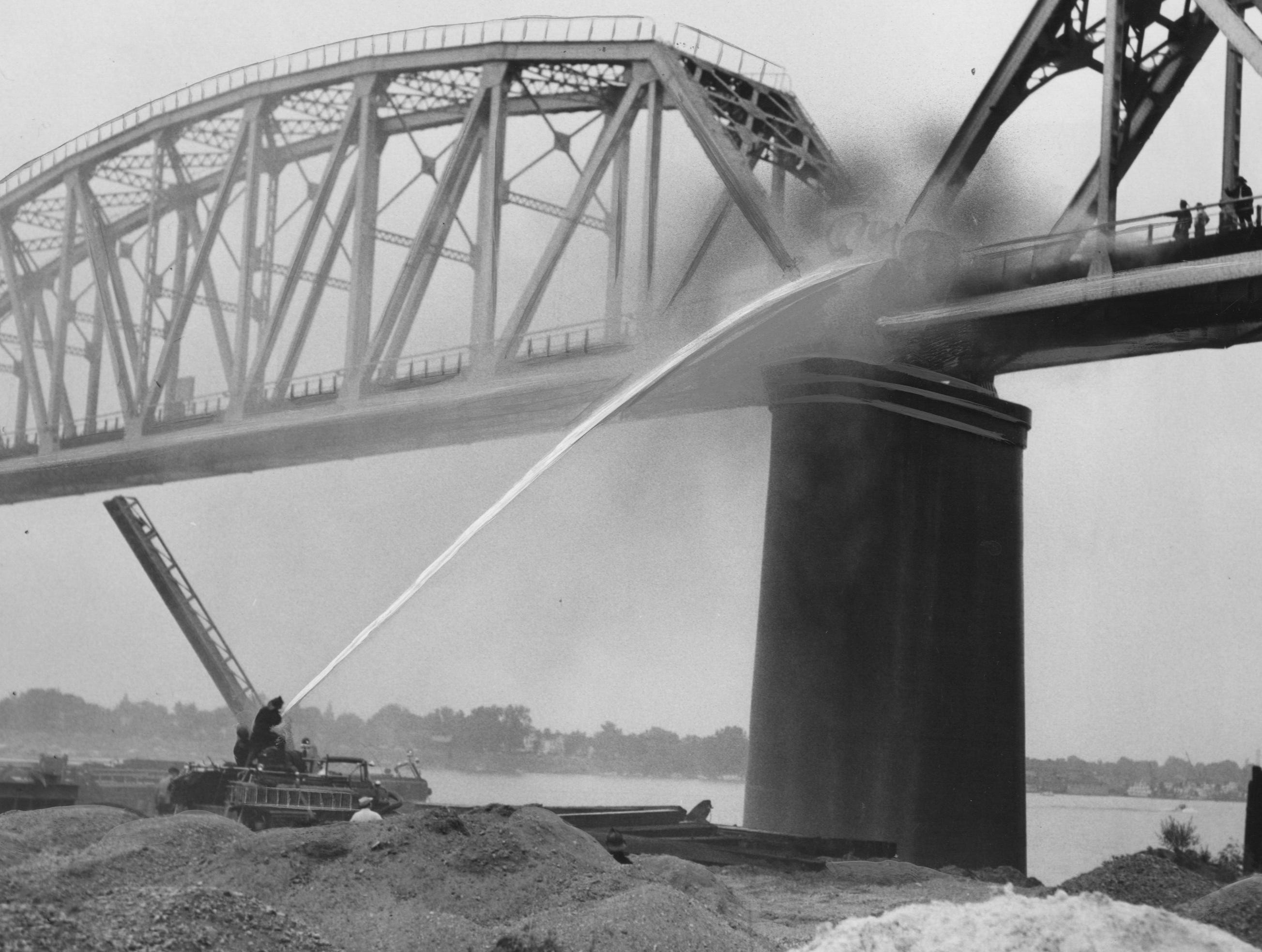 Long-range accuracy was necessary as firemen played water on burning crosswise of the Big Four Railroad Bridge at River Road near Campbell last night. 