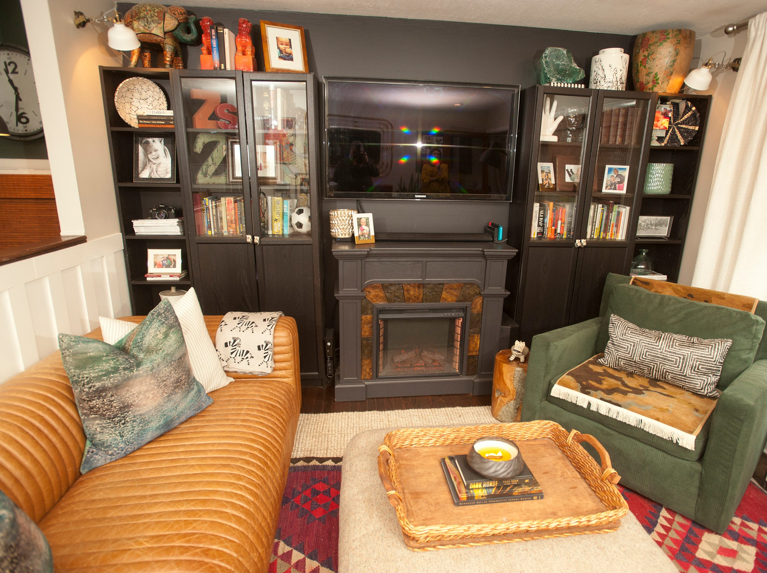 Professional home decorator Skye Squires' Hikes Point living room includes a black wall of built-in bookcases, electric fireplace and large screen television (which is black when it is off.)