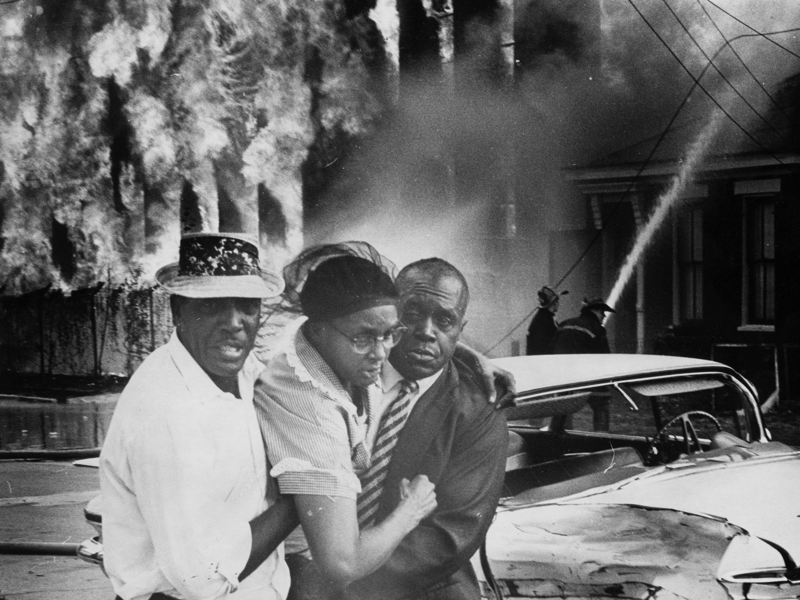 A nearby resident is helped from a fire at old Woolen Mills at  Clay and Caldwell. 