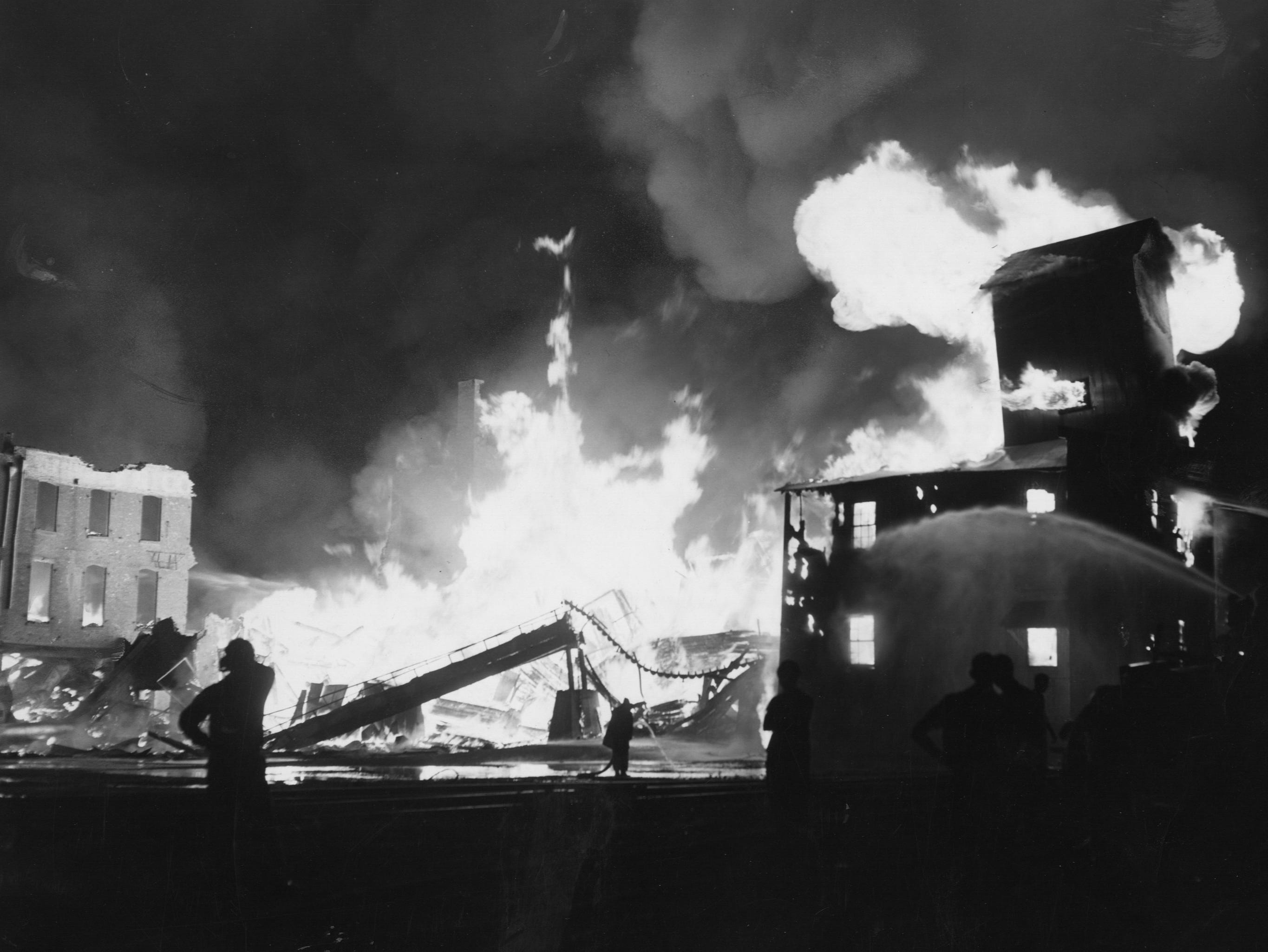 Flames and smoke silhouette gnarled ruins of a feed company. 