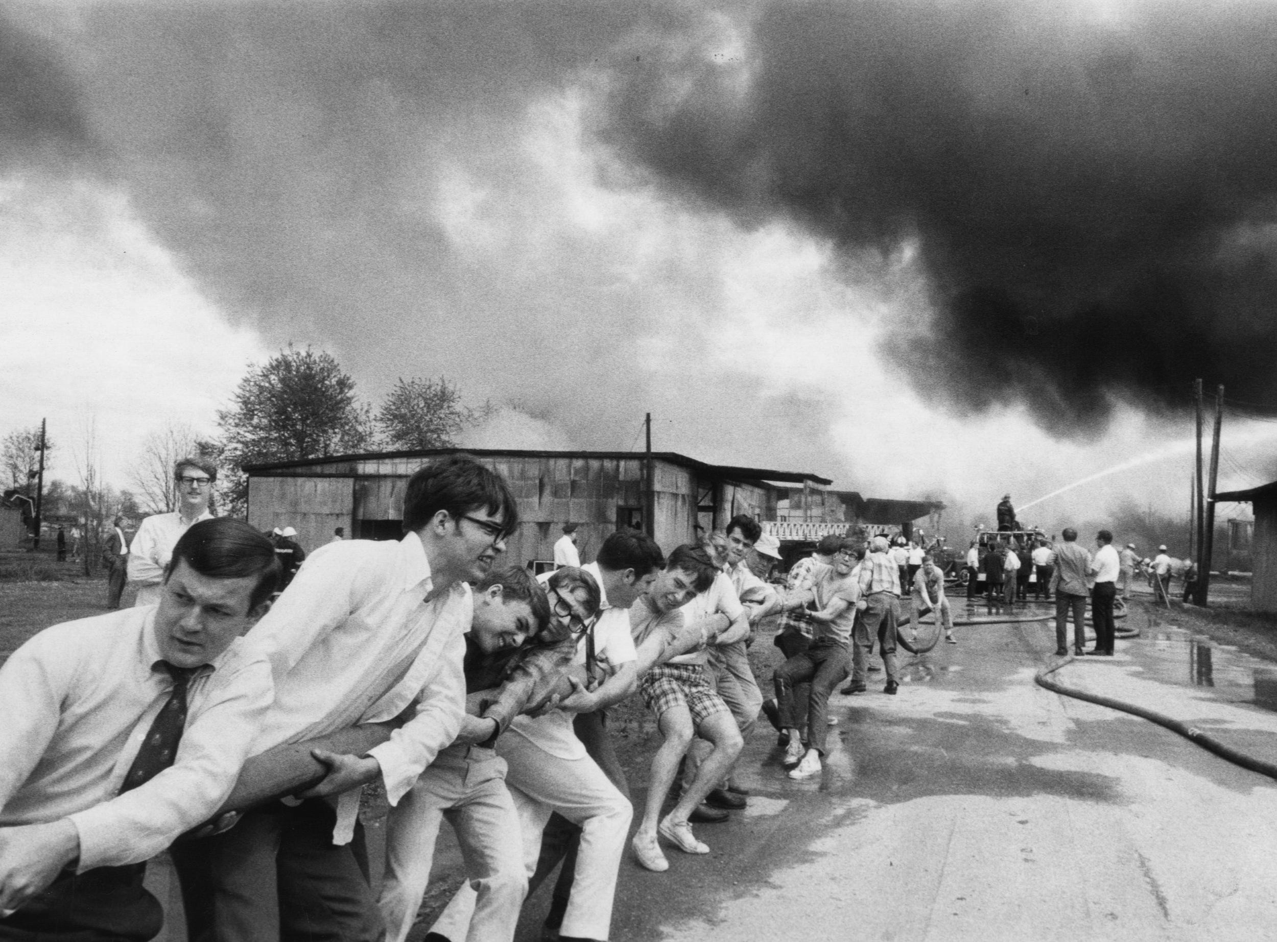 An empty tobacco warehouse burns out of control as neighborhood young people aid Louisville firemen by pulling additional hose to spectacular fire at the Seventh Street Road Tobacco Warehouse. 