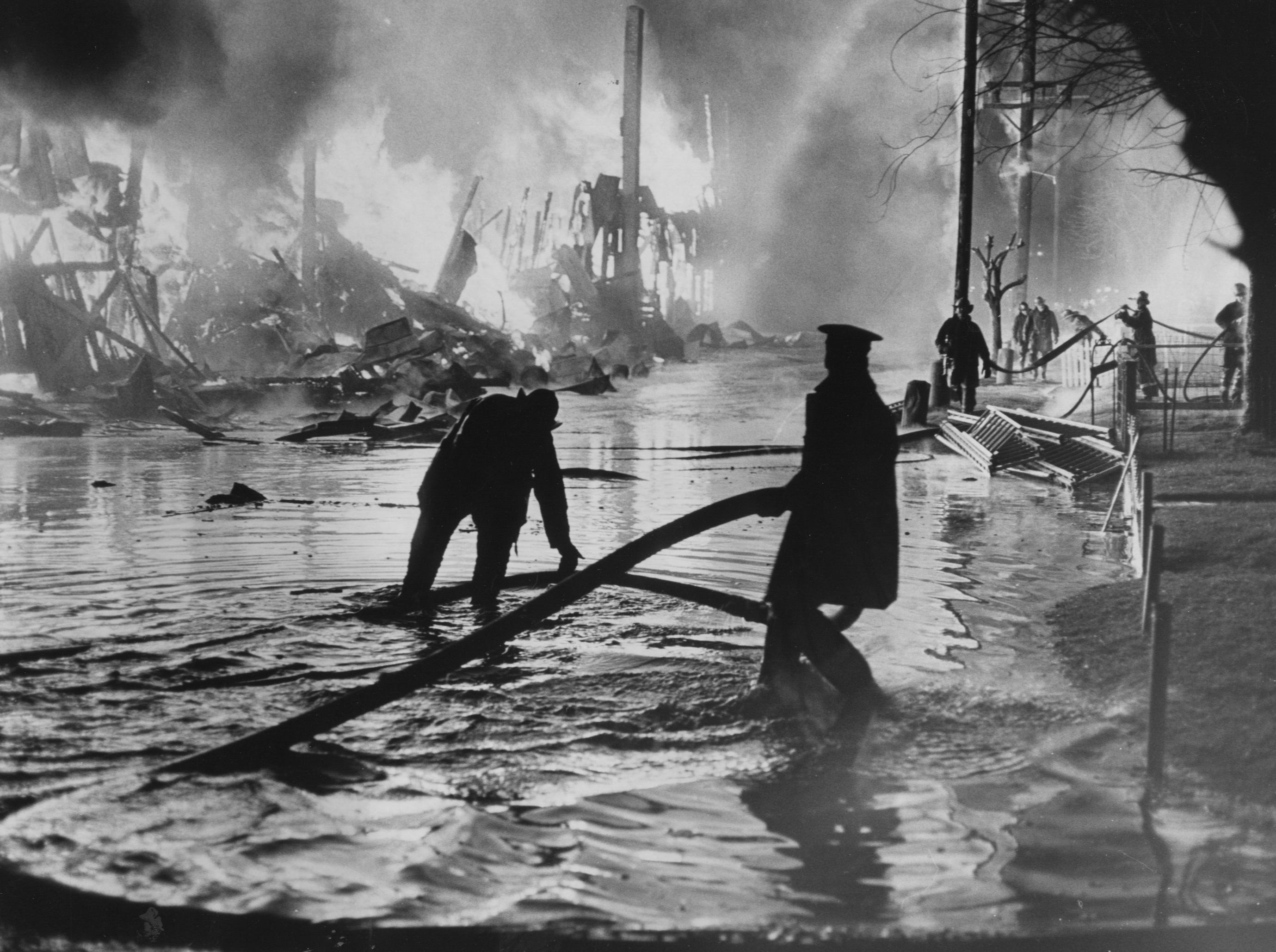 Standing ankle deep in water, firemen move hoses into position to fight a four-alarm blaze that destroyed a warehouse of the Louisville Sash & Door Co. last night. 