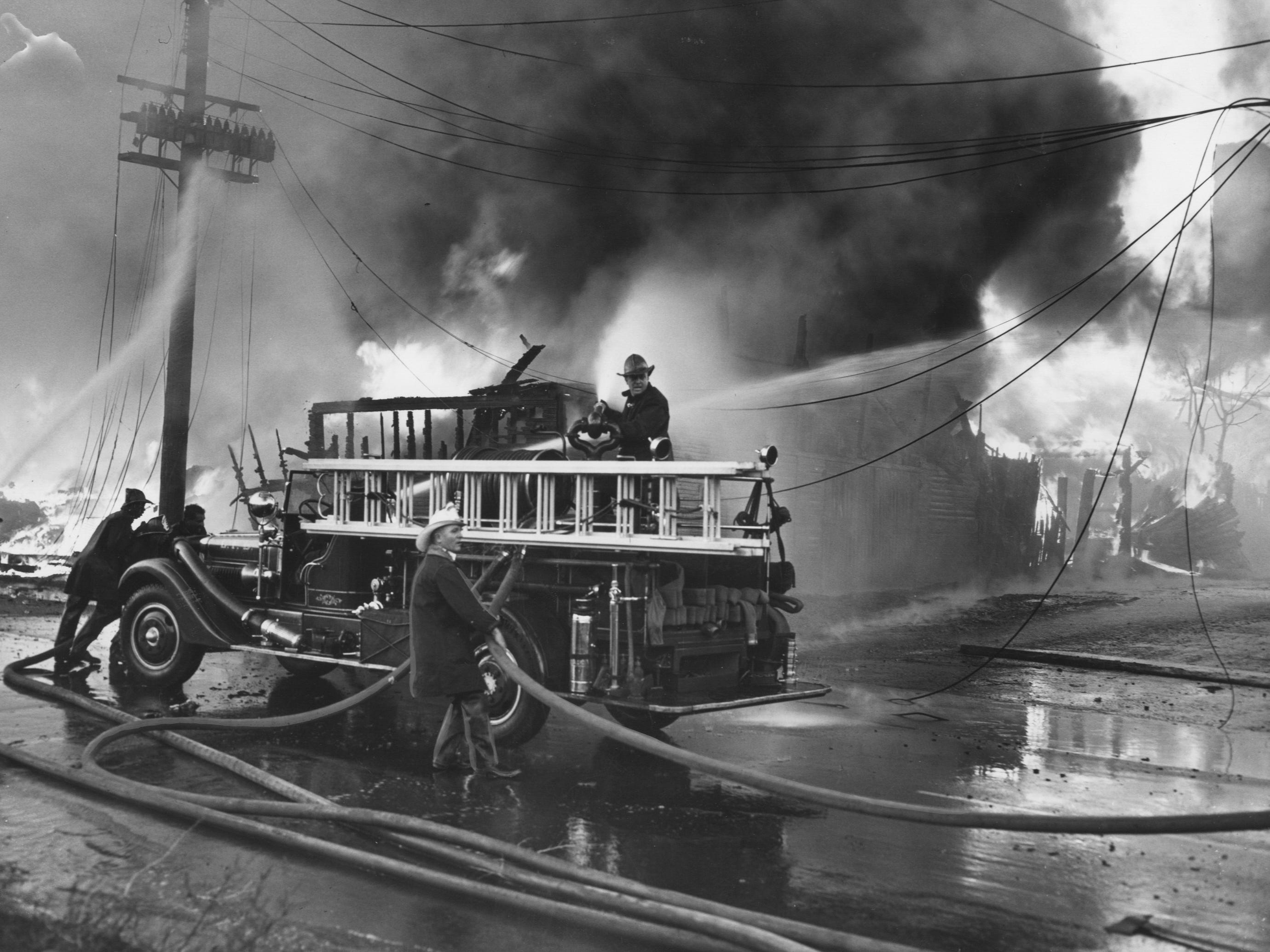 Drooping electric wires form a menacing backdrop as firemen struggle with hose at a warehouse fire at 12th and Wilson. 