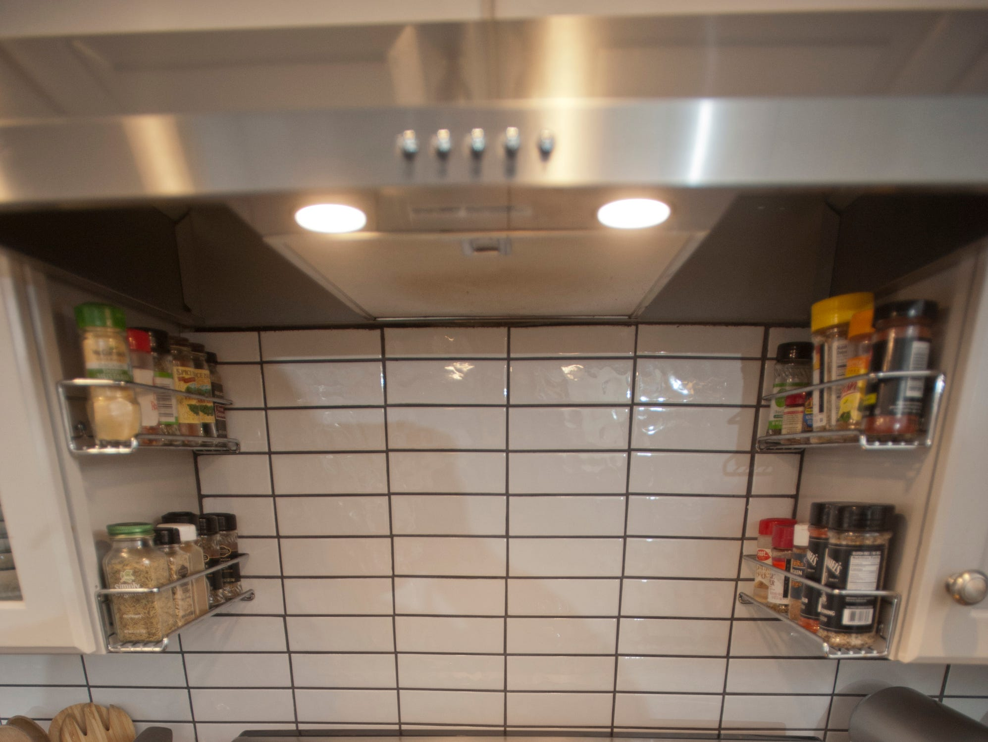 The kitchen gas range uses a grid patterned ceramic subway tile.
