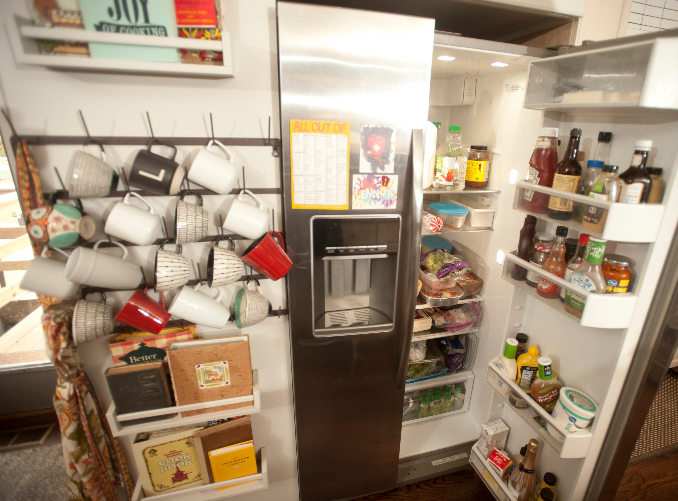 The Squires kitchen includes a wall for cookbooks and cups which stands next to the kitchen refrigerator.