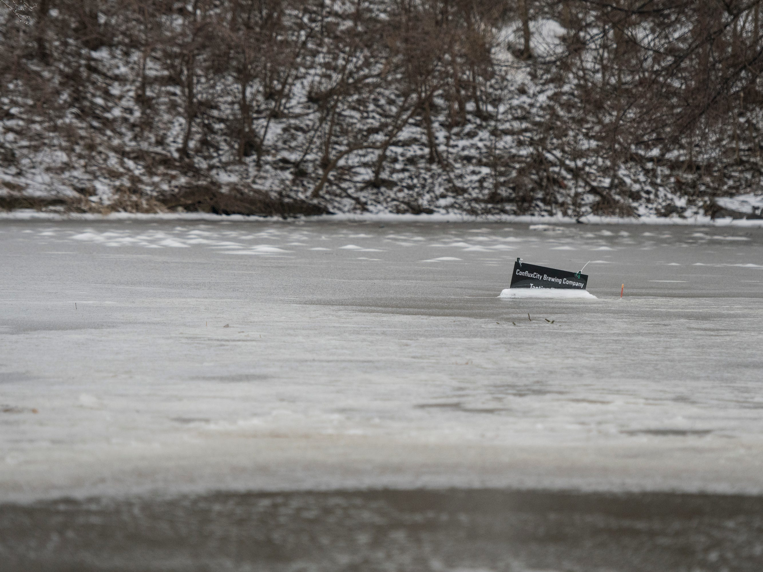 Signage under ice in the parking lot of ConfluxCity Brewing Co. in downtown Portland, Michigan, Wednesday morning, Feb. 6, 2019.  About 50 people were evacuated late Tuesday evening through early Wednesday morning due to flooding along the Grand River caused by melting snow and an ice jam in the river.  [Matthew Dae Smith/Lansing State Journal]