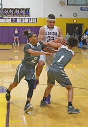 Lexington's Cade Stover is guarded closely by Madison's Jashawn Au and Jayondrae Jones on Tuesday night at Lexington High School.