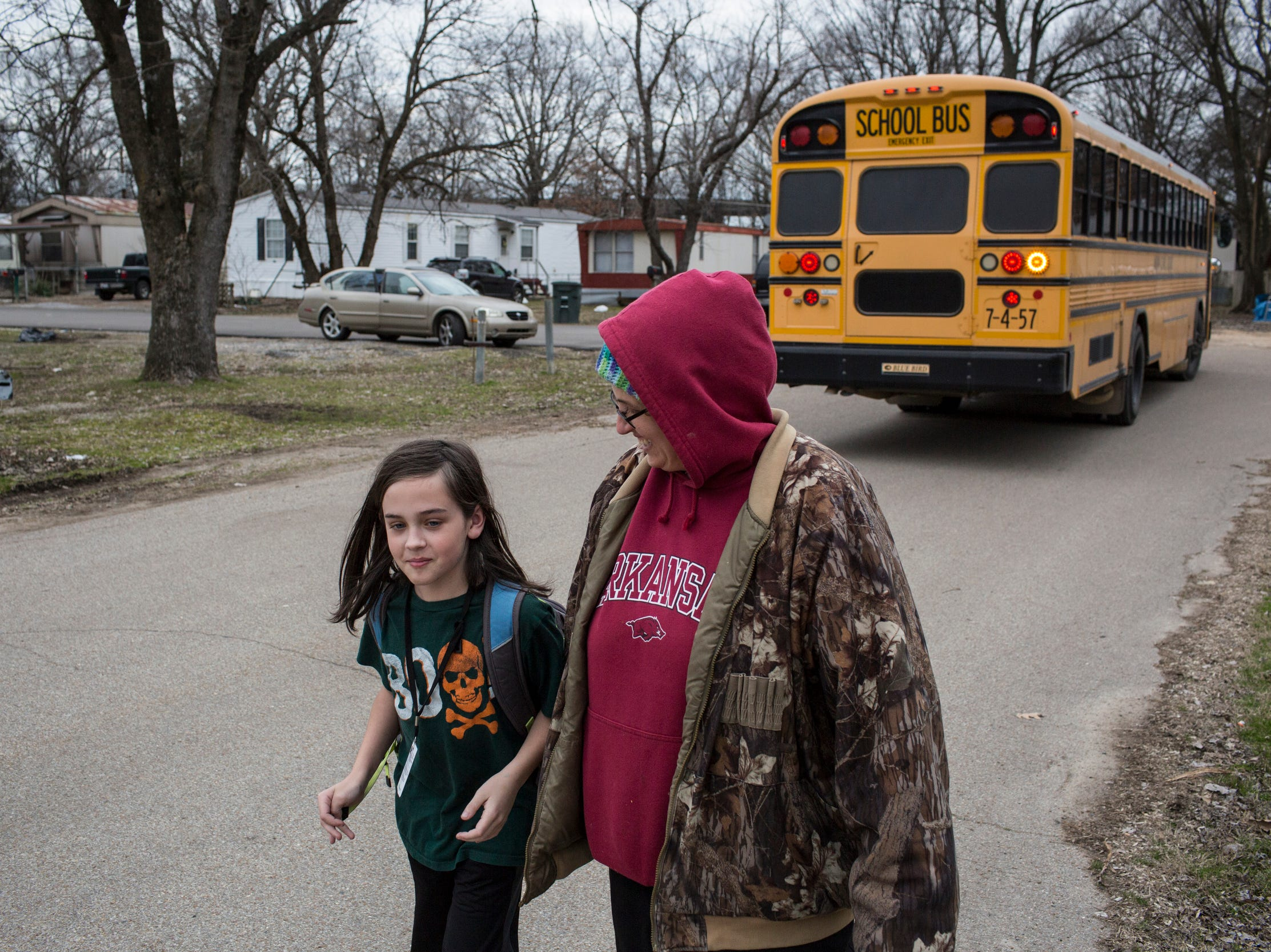 """January 31, 2019 - Debbie Camp walks her son, Logan Holt, 11, home from the bus stop in Lakeshore. In December of 2017, Debbie Camp, a mother of three who owns a trailer in Lakeshore, called the Arkansas Department of Environmental Quality to complain, """"Sewage is running everywhere.""""  She said she's frustrated that she hasn't seen any follow-up. """"Nobody cares, just cause we're a trailer park,"""" Camp said. Records obtained by The CA show that Camp's complaint was received. But, the Arkansas Department of Environmental Quality said they have no inspection report resulting from her complaint, though they believe the issue was related to a residential line as opposed to the main sewer."""
