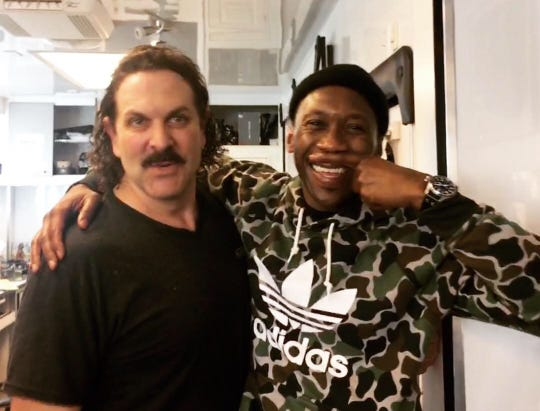 "Mahershala Ali creates his own ""mustache"" while posing with David Kallaway on the set of ""Green Book."""