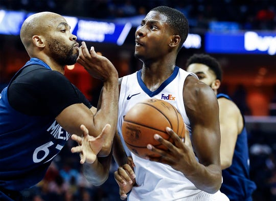 Memphis Grizzlies center Jaren Jackson Jr. (right) drives the lane against Minnesota Timberwolves defender Taj Gibson (right) during action at the FedExForum in Memphis, Tenn., Tuesday, February 5, 2019.