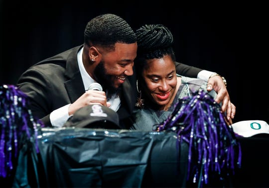 Southwind defensive tackle Kristian Williams (left) hugs his mother Kabrina Pleas after he signed with Oregon during a ceremony at the high school Wednesday morning.