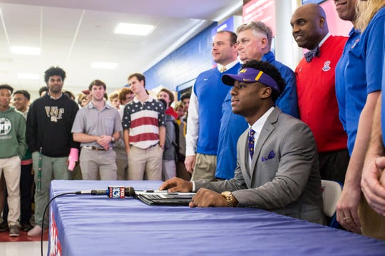 MUS' Maurice Hampton poses for a photo with football coaches Wednesday after announcing that he signed to play for LSU.