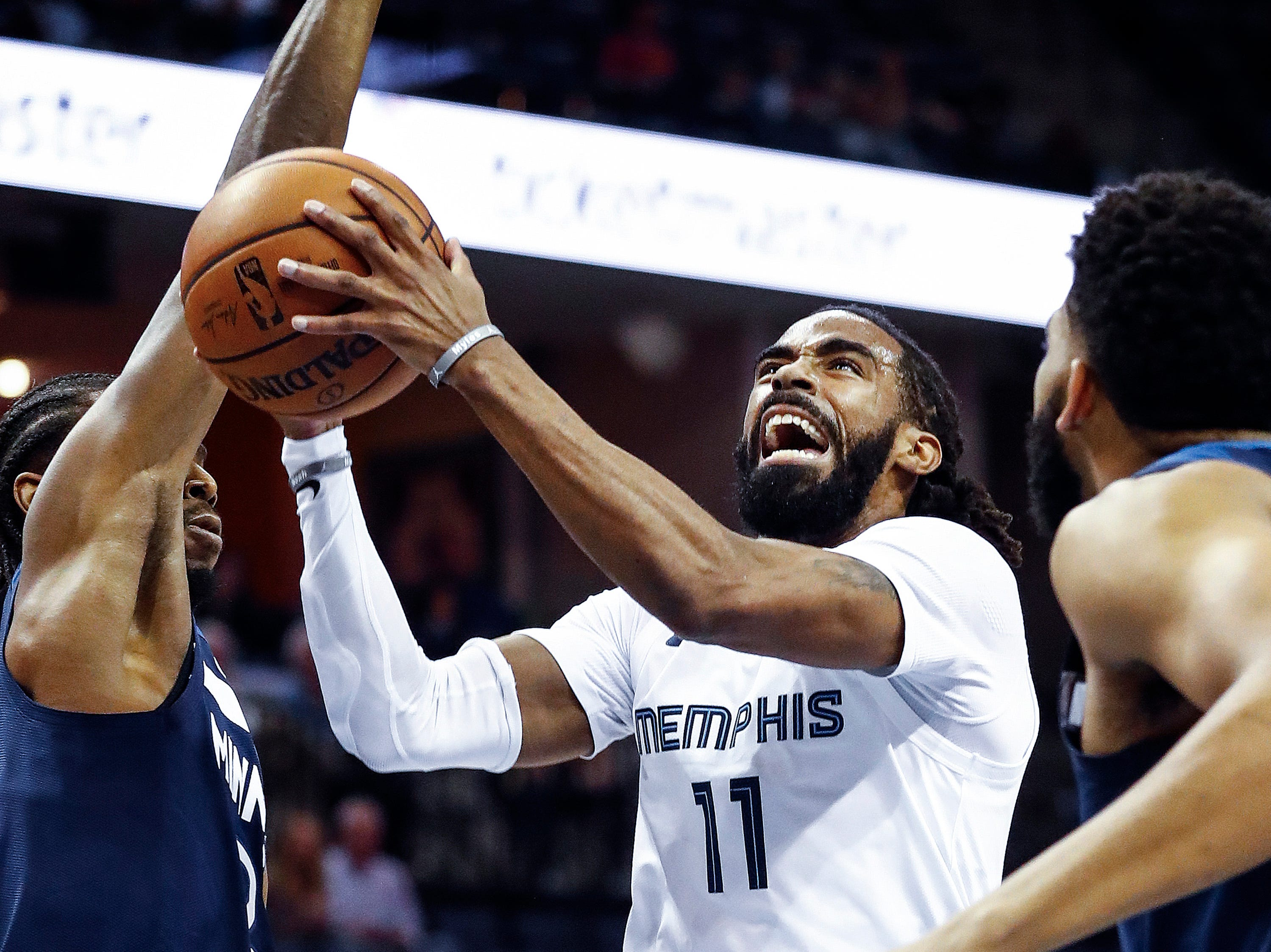 Memphis Grizzlies guard Mike Conley drives the lane against the Minnesota Timberwolves defense during action at the FedExForum in Memphis, Tenn., Tuesday, February 5, 2019.