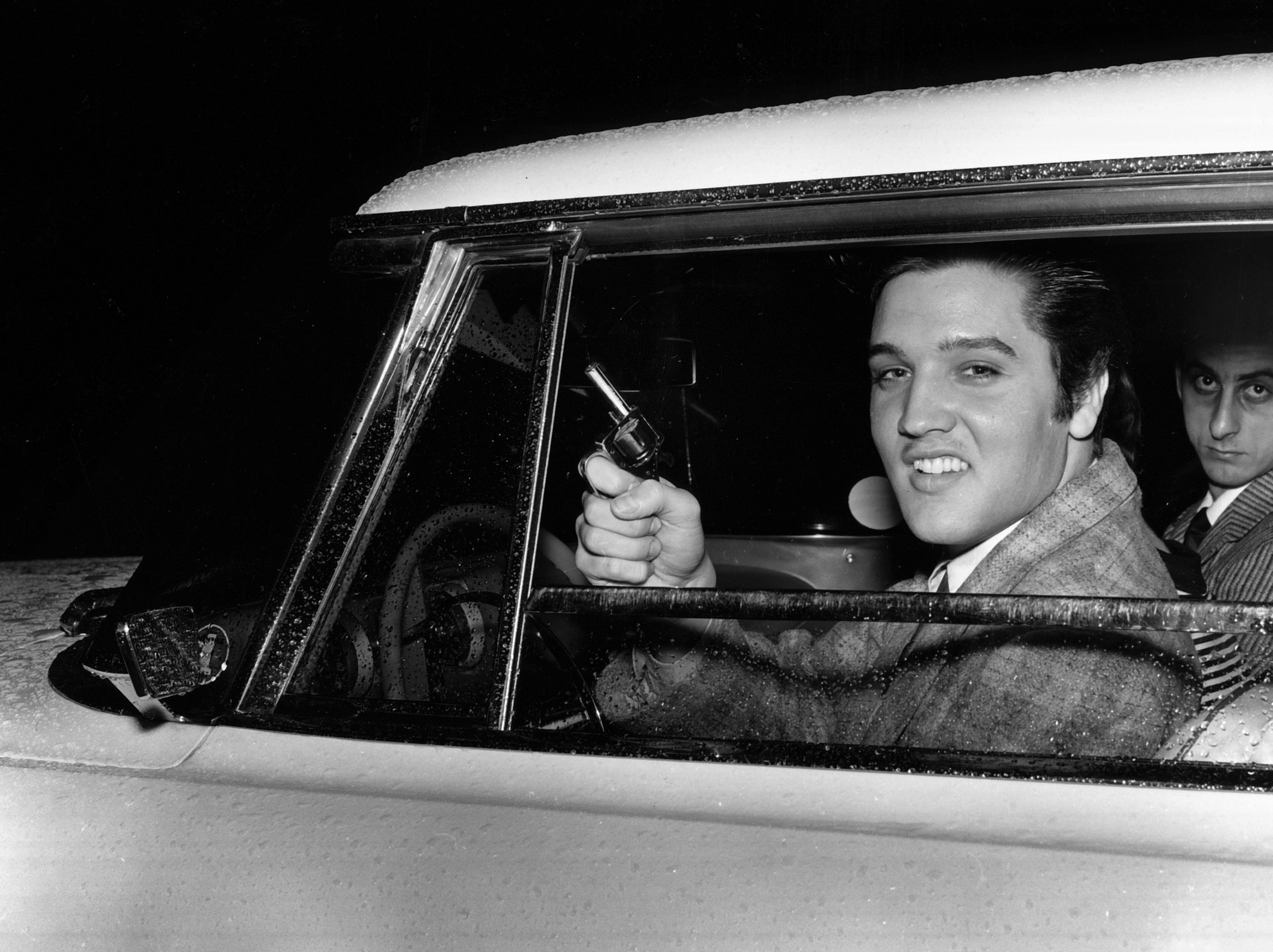 """Elvis Presley displays a toy pistol, used as a prop in a movie, that caused trouble on the night of March 22, 1957 when a Marine from Millington tried to """"pick a fight with me."""" The singer pulled the gun out of his coat to scare the Marine away. By the following Tuesday, Elvis and the Marine, Pfc. Hershel Nixon, had patched up the quarrel. """"It was all a misunderstanding,"""" said Presley. """"We're both sorry it happened."""" Elvis' friend George Klein is in the passenger seat."""