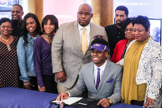 MUS's Maurice Hampton poses for a photo with family after announcing that he signed to play college football for LSU.