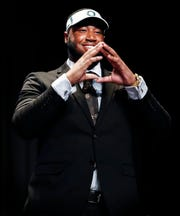 "Southwind defensive tackle Kristian Williams throws up the ""O"" sign after signed with Oregon, during a ceremony at the high school Wednesday morning."