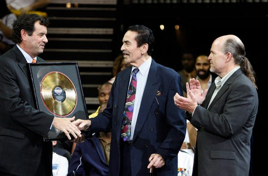 Mike Redlick, left, Memphis Grizzlies senior vice president for corporate partnership, presents music producer Willie Mitchell, center, with an award from the Memphis Rock 'n' Soul Museum in honor of the 50th anniversary of Mitchell's HI Records, Thursday, March 22, 2007, at an NBA basketball game between the Grizzlies and the Los Angeles Lakers. John Doyle, also representing the museum, applauds at right.