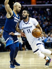 Memphis Grizzlies guard Mike Conley (right) drives the lane against Minnesota Timberwolves defender Jerryd Bayless (left)  during action at the FedExForum in Memphis, Tenn., Tuesday, February 5, 2019.
