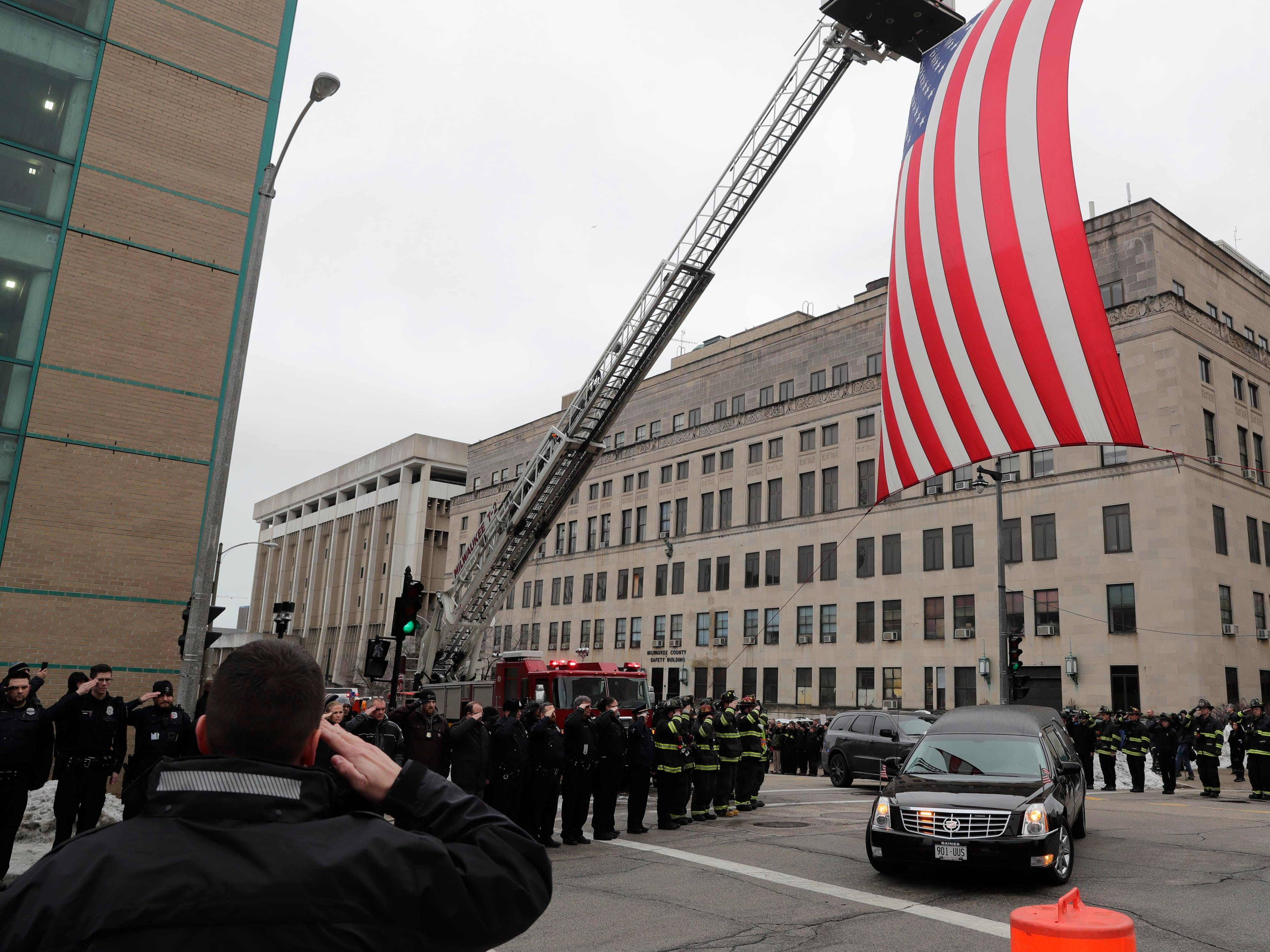 The hearse containing the body of the officer passes under a flag that was raised by The Milwaukee Fire Department at the intersection of 9th and State streets.