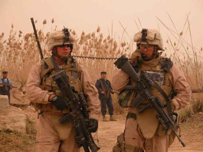 Cpl. Jose Gonzalez (right), 24, of Kenosha talks on a radio carried by Lance Cpl. Terry Medema, 24, of Waupun. Gonzalez was calling his commander to report the rocket discovery by Iraqi police on the bank of the Euphrates River near Hamimiyah in Anbar Province.
