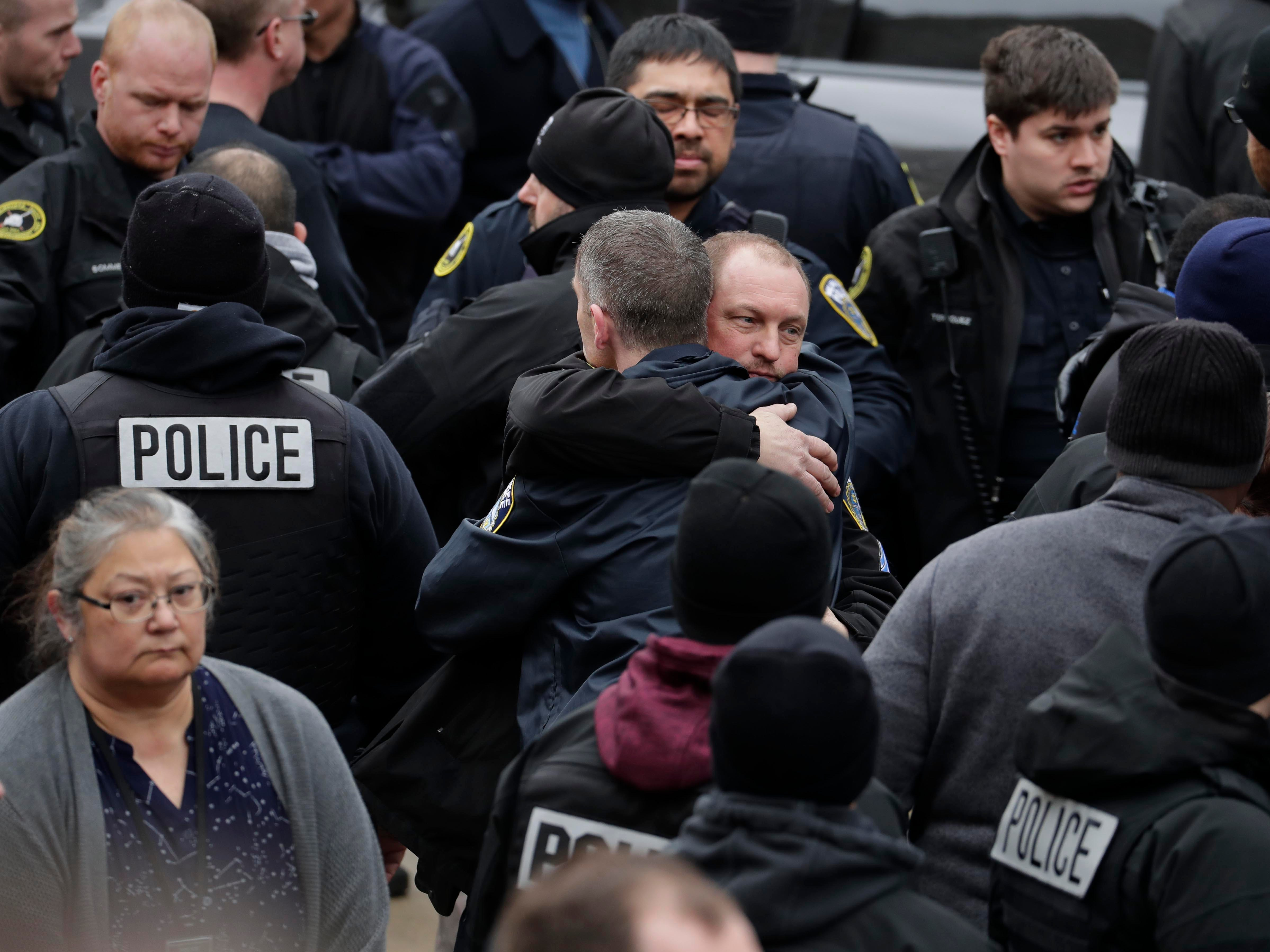 Milwaukee police officers comfort each other as they waited for the body of their fallen comrade to arrive at the county medical examiner's office Wednesday.