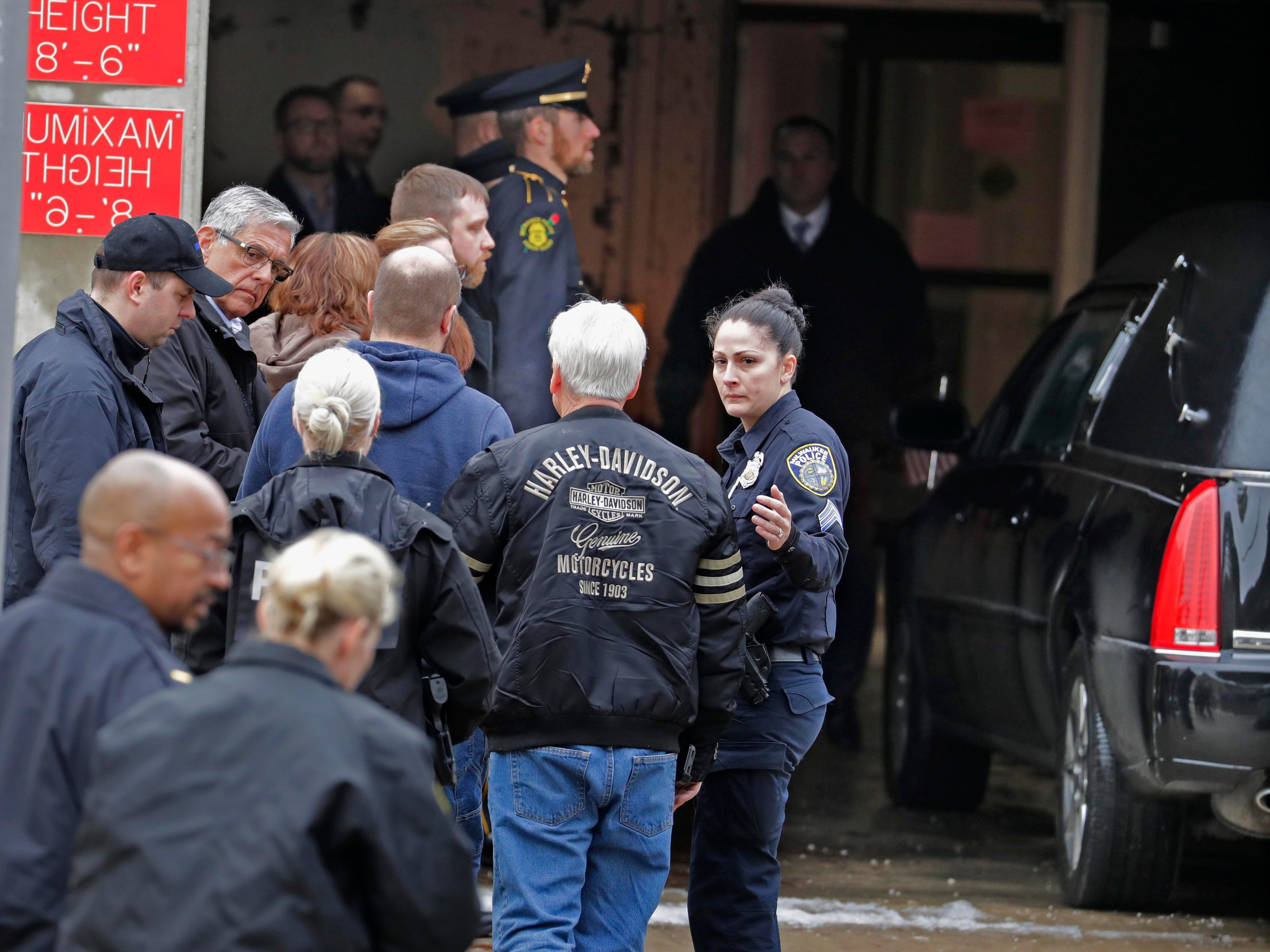 Police officers, friends and possibly family members watch as the hearse arrived at the Milwaukee County Medical Examiner's Office on Wednesday.