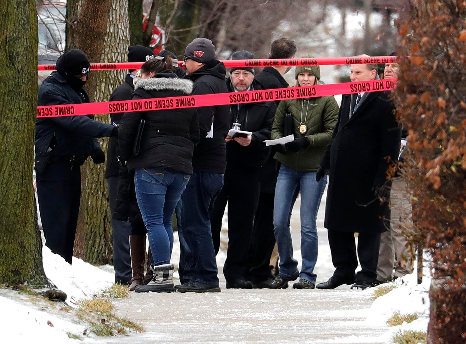 Milwaukee police inspectors gather in front of a home near South 12th and West Dakota streets that was taped off as a crime scene  Wednesday after a Milwaukee police officer was shot. The officer, who was shot with a high-powered rifle, died.