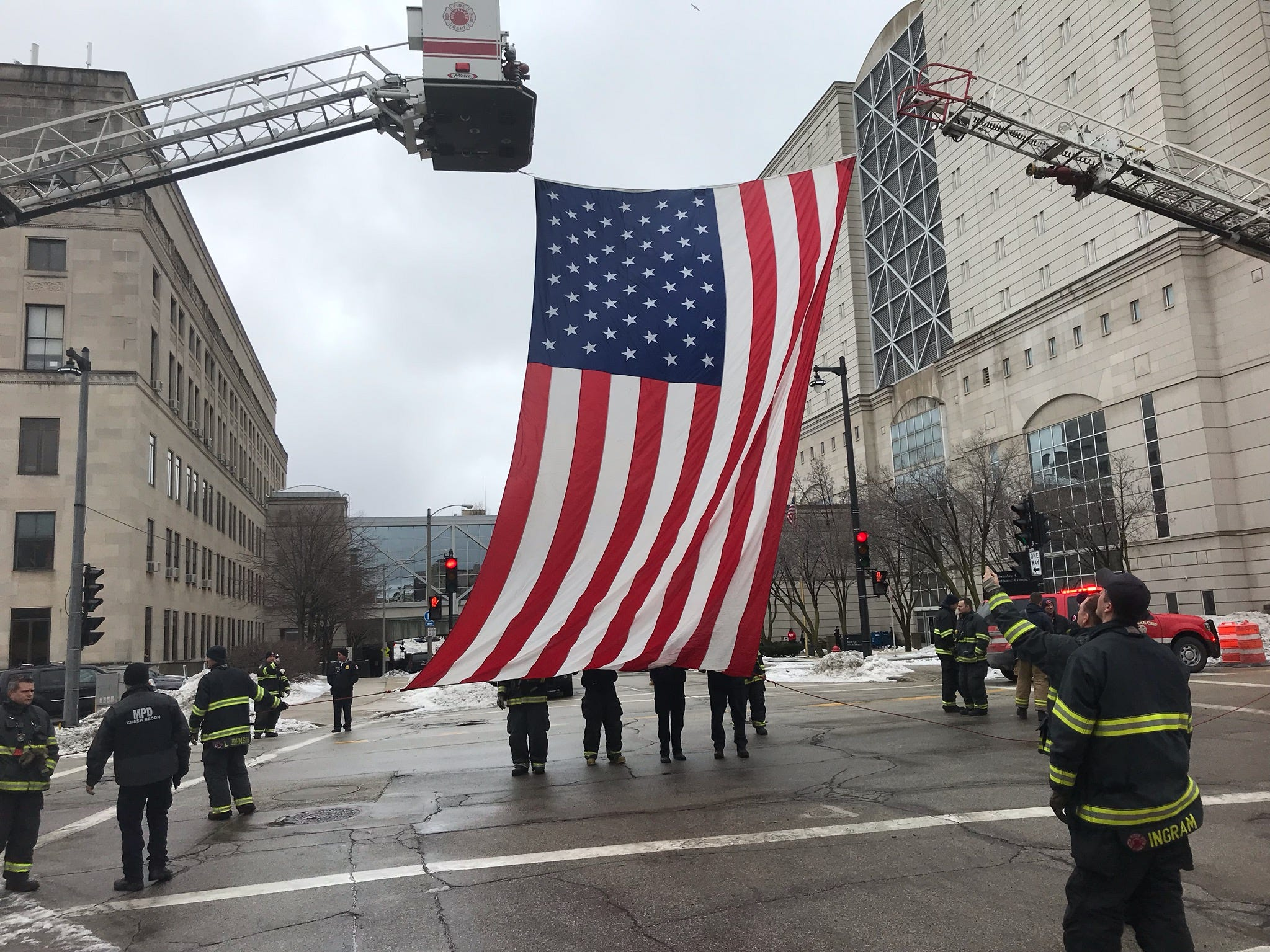 The Milwaukee Fire Department raises a flag at the intersection of 9th and State streets.