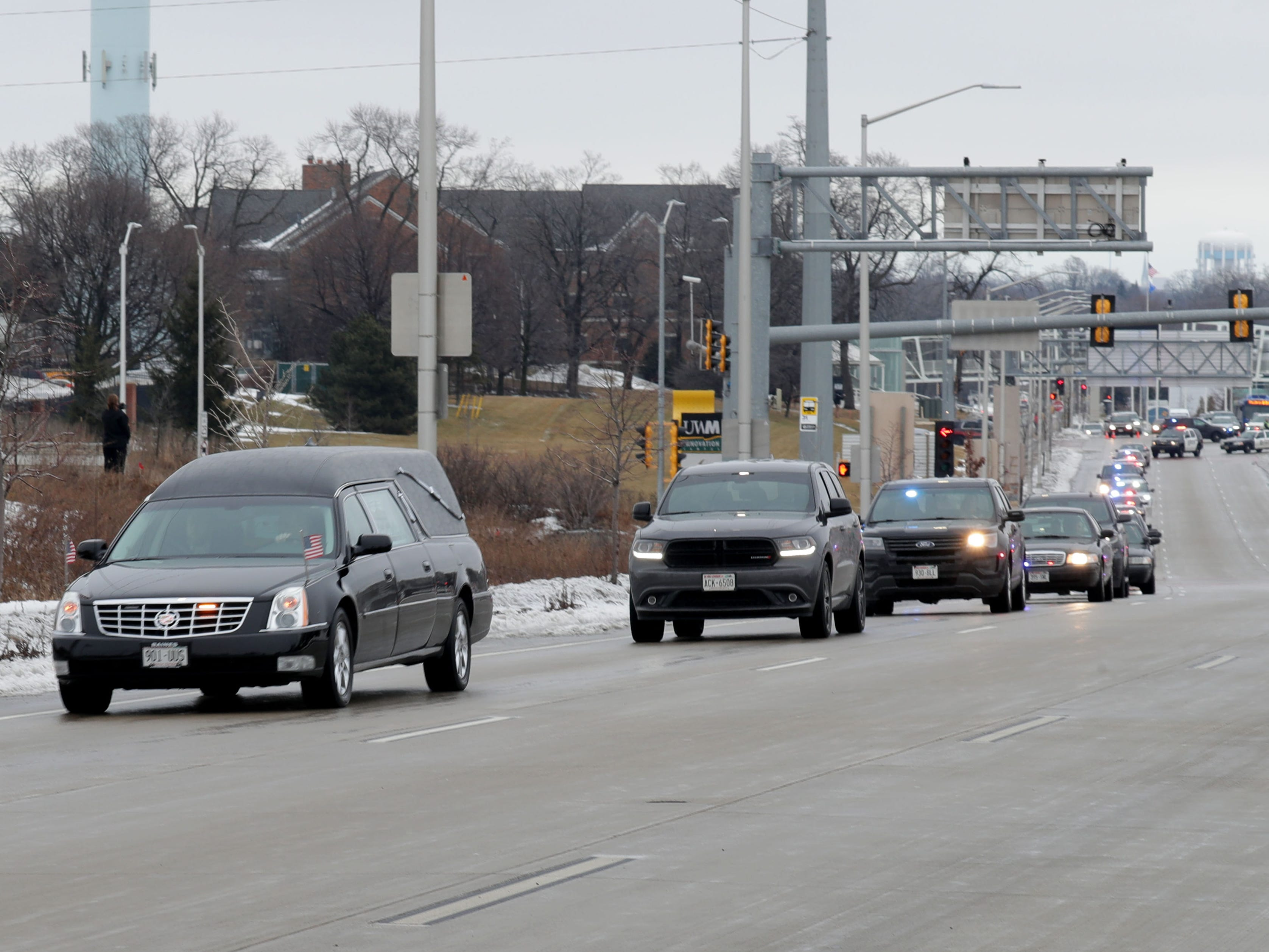 A hearse is seen in the procession as police vehicles leave Froedtert Hospital in Wauwatosa on Wednesday on its way to the Milwaukee County Medical Examiner's Office with the hearse containing the body of a fallen Milwaukee police officer.
