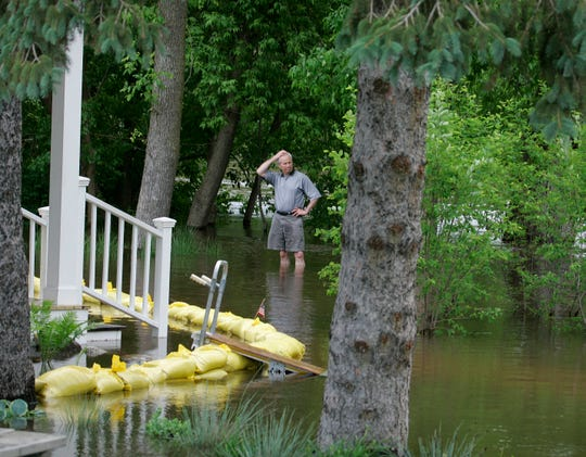 Ray Marcy, owner of the building that houses his daughter, Lynn Wroblewski's Fiddleheads Espresso Bar and Grille in Thiensville, surveys floodwaters from the Milwaukee River as they rose outside the building in June 2008.