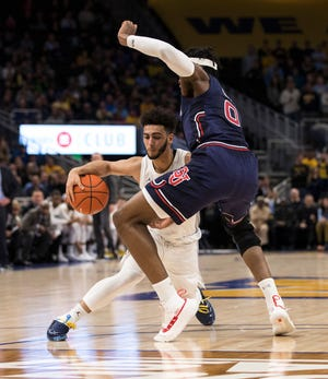 Marquette guard Markus Howard puts a move on St. John's forward Sedee Keita.