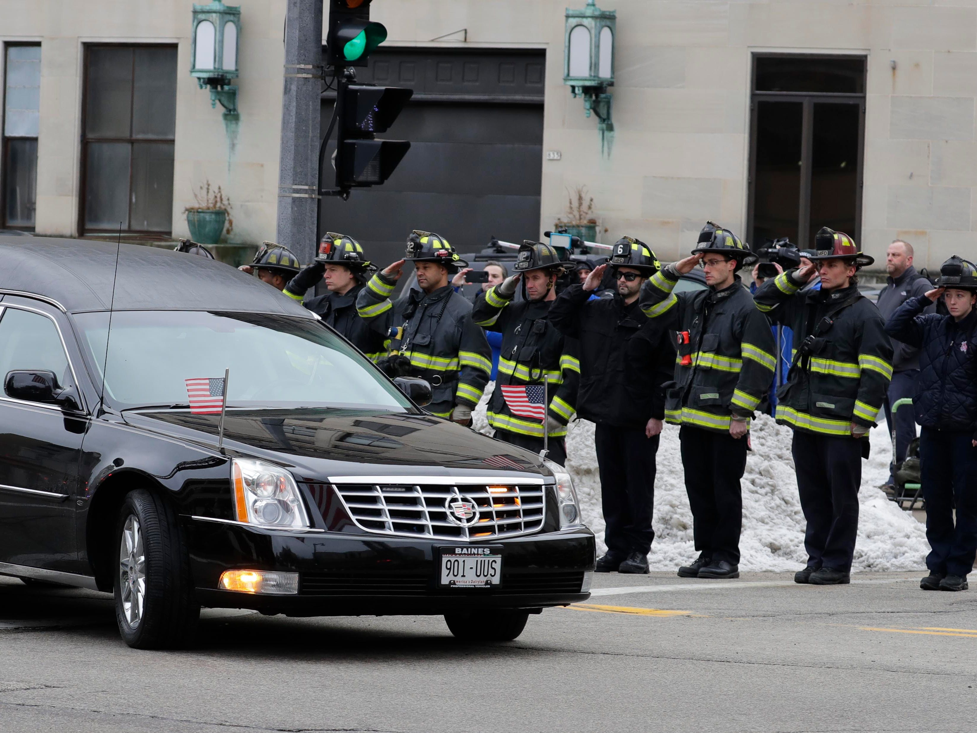 The hearse containing the body of the officer passes the intersection of 9th and State streets.
