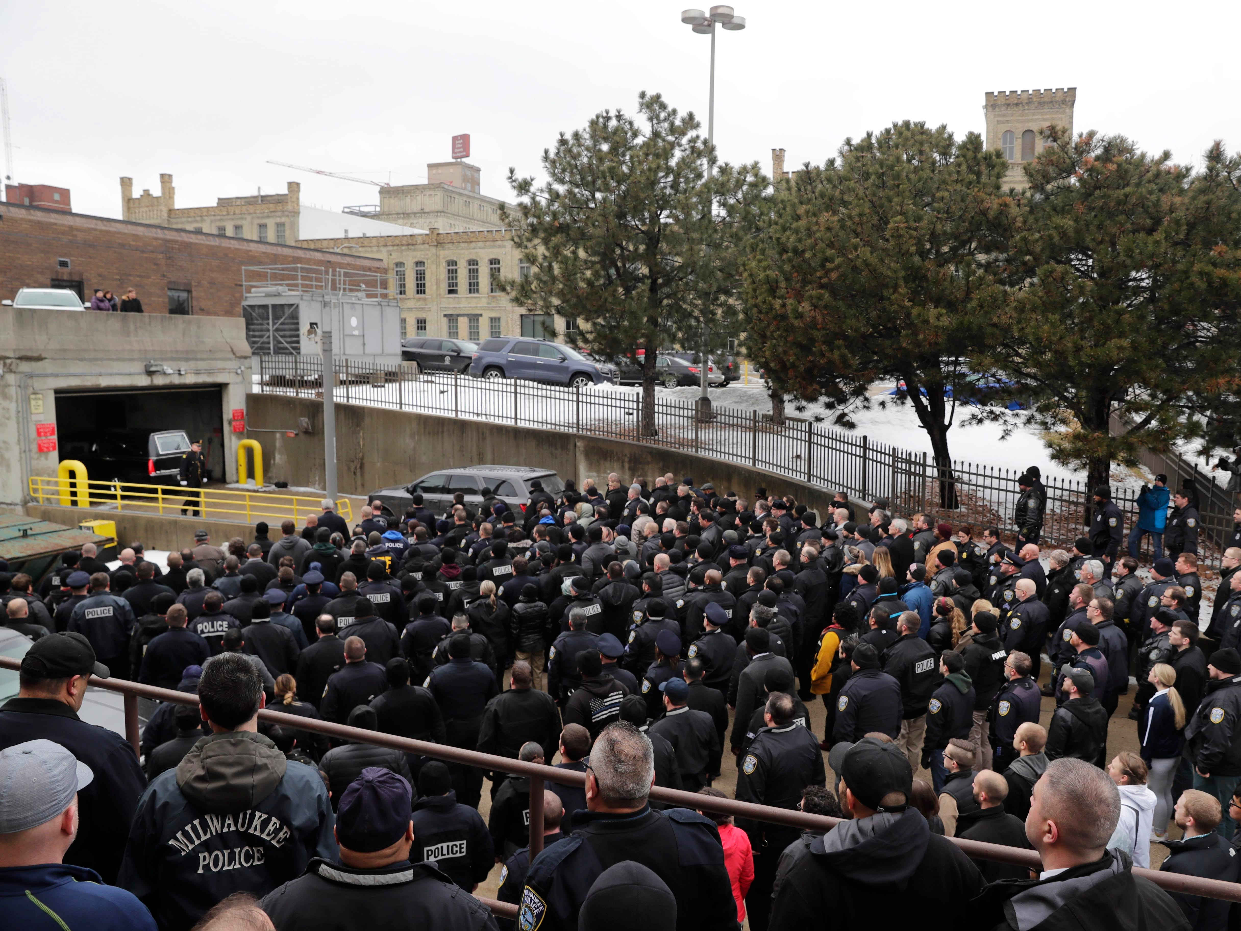 Hundreds of police officers fill the back entrance to the Milwaukee County Medical Examiner's Office as the hearse carrying the body of their fallen comrade arrives Wednesday.