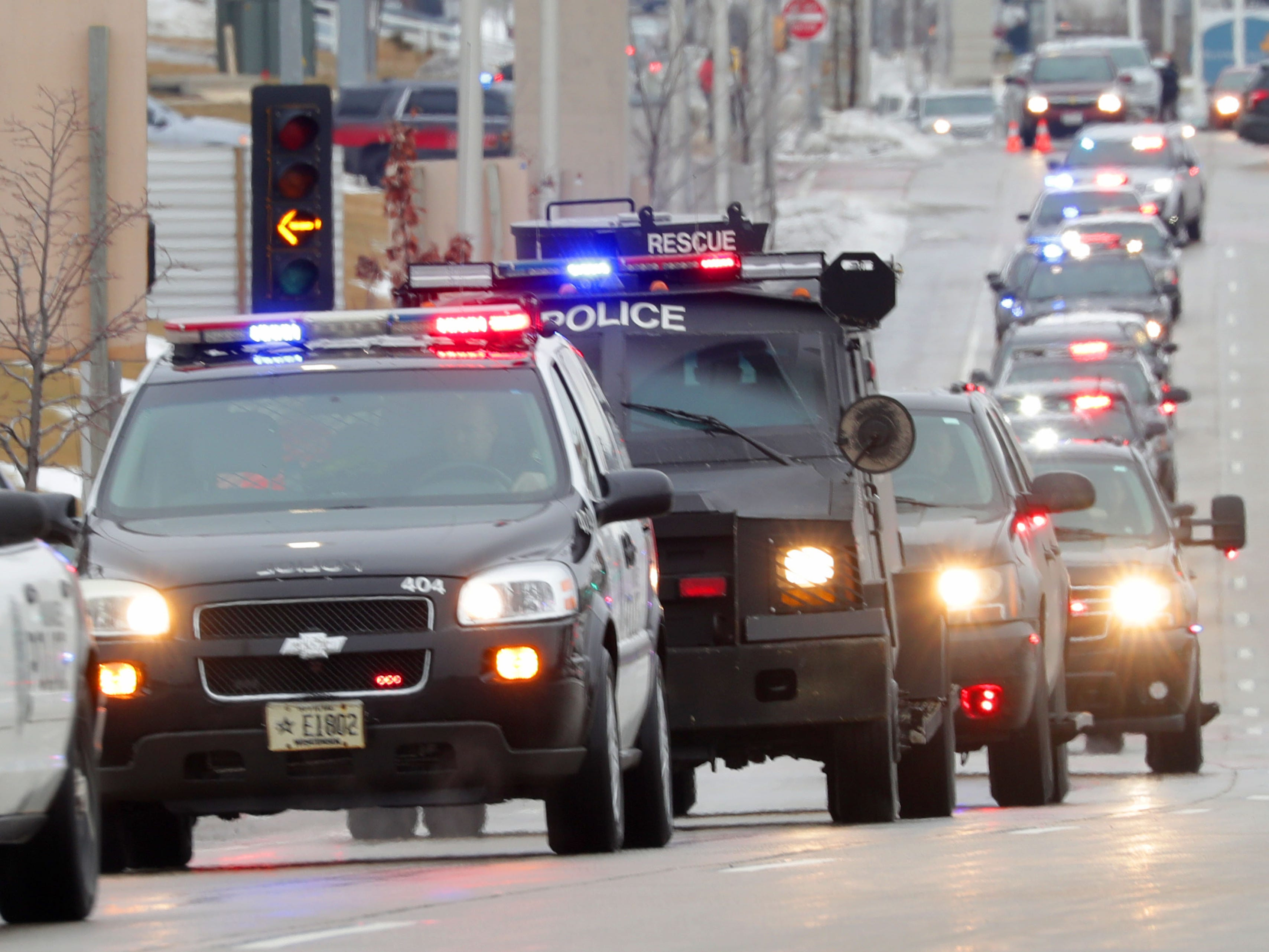 A procession of police vehicles including an armored vehicle leaves Froedtert Hospital in Wauwatosa on Wednesday on its way to the Milwaukee County Medical Examiner's Office with the hearse containing the body of a fallen Milwaukee police officer.
