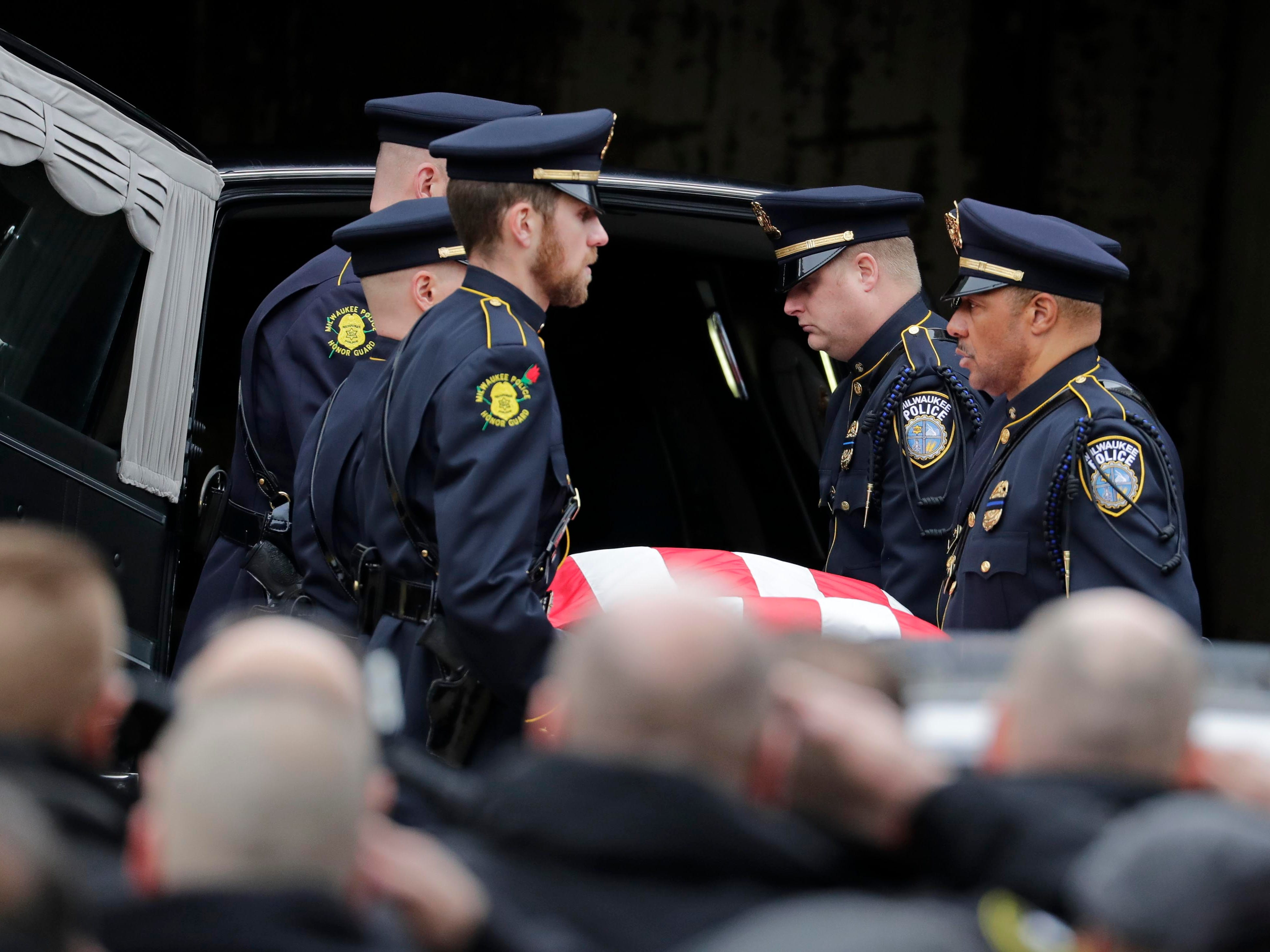 An honor guard removes the casket  carrying the body of the fallen Milwaukee police officer from the hearse after it arrived at the county medical examiner's office on Wednesday.