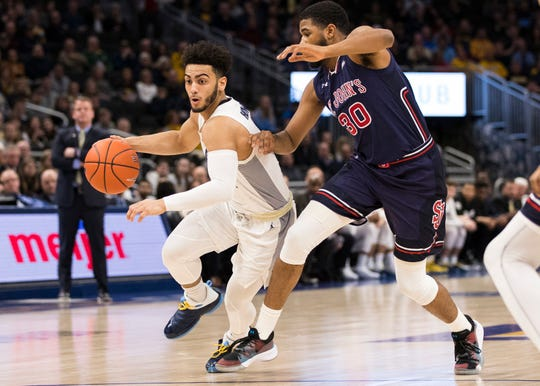 Marquette guard Markus Howard (0) drives for the basket around St. John's  guard LJ Figueroa in the first half on Tuesday.