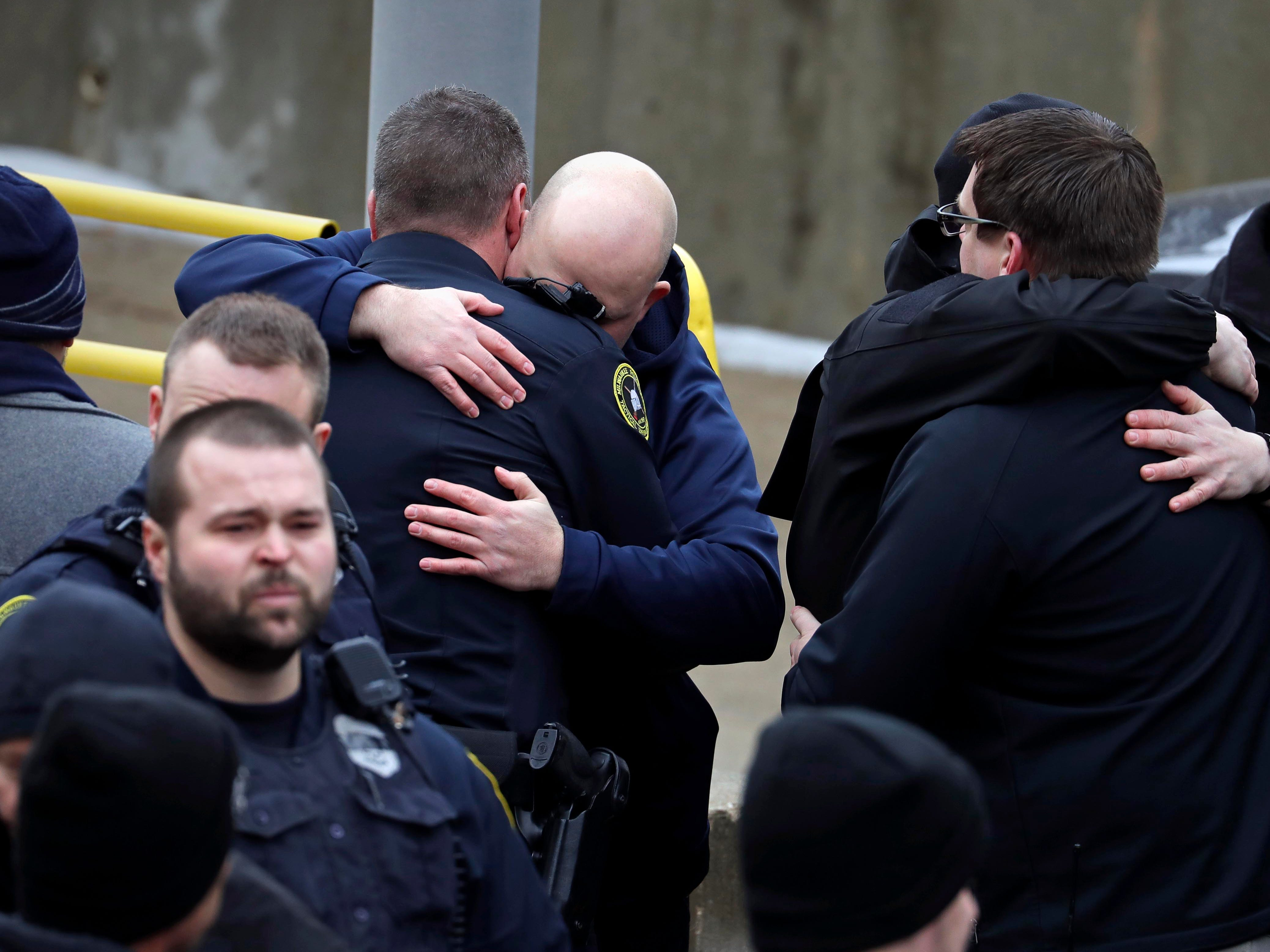 Milwaukee police officers comfort each other as they wait for the body of their fallen comrade to arrive at the county medical examiner's office Wednesday.