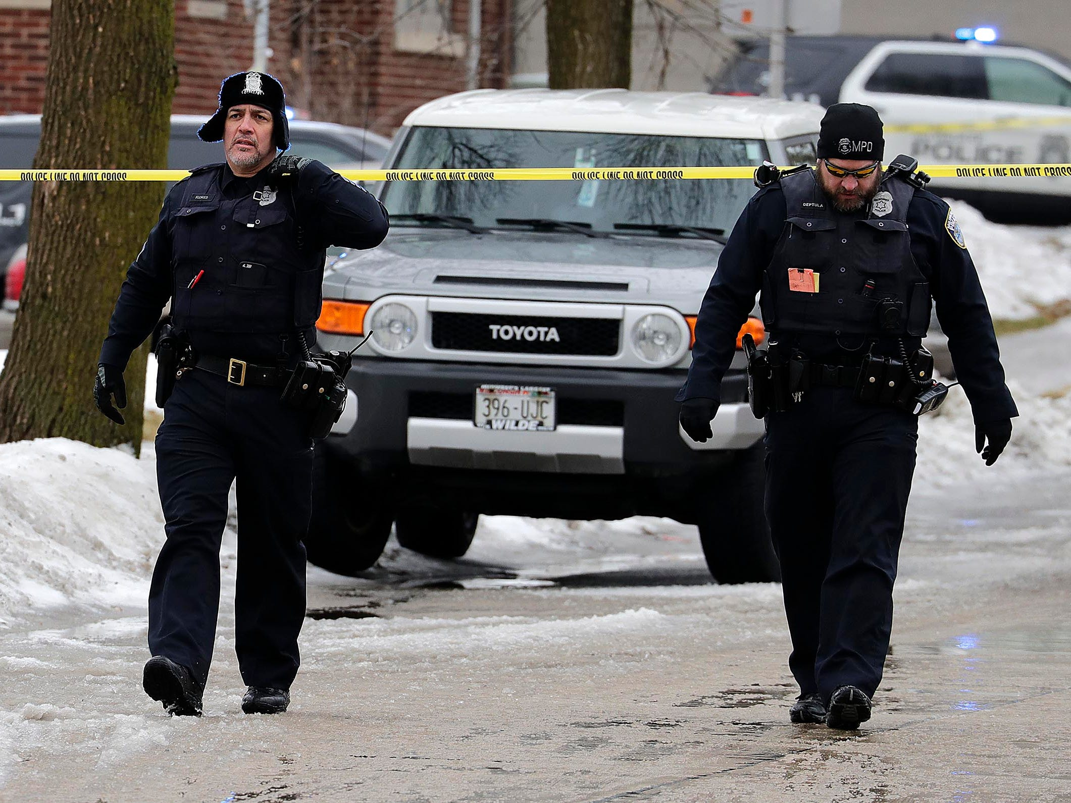 Milwaukee police officers leave the scene where a Milwaukee Police officer was shot Wednesday morning on the city's south side. The officer died.