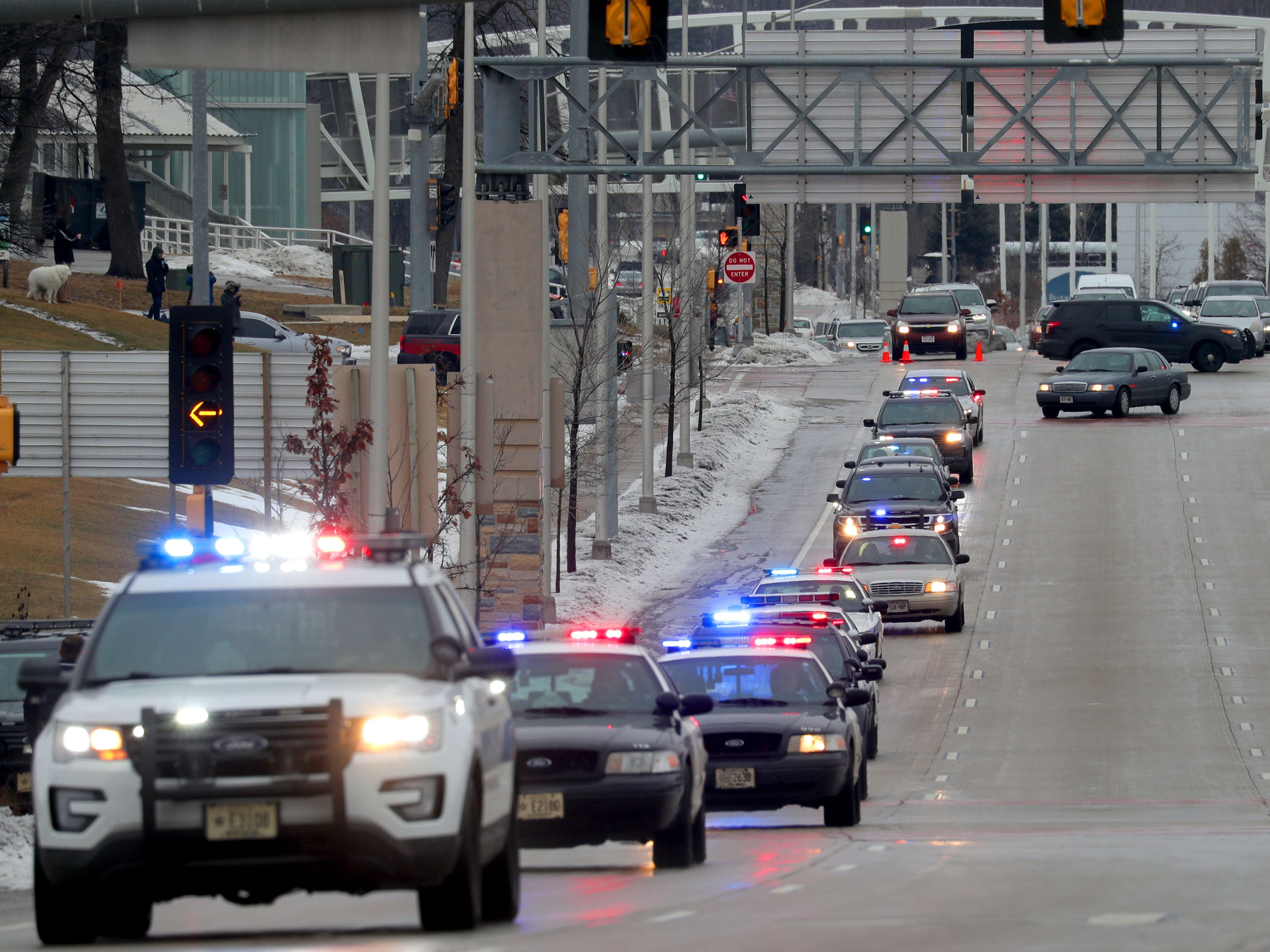 A procession of police vehicles leaves Froedtert Hospital in Wauwatosa on Wednesday on its way to the Milwaukee County Medical Examiner's Office with the hearse containing the body of a fallen Milwaukee police officer.