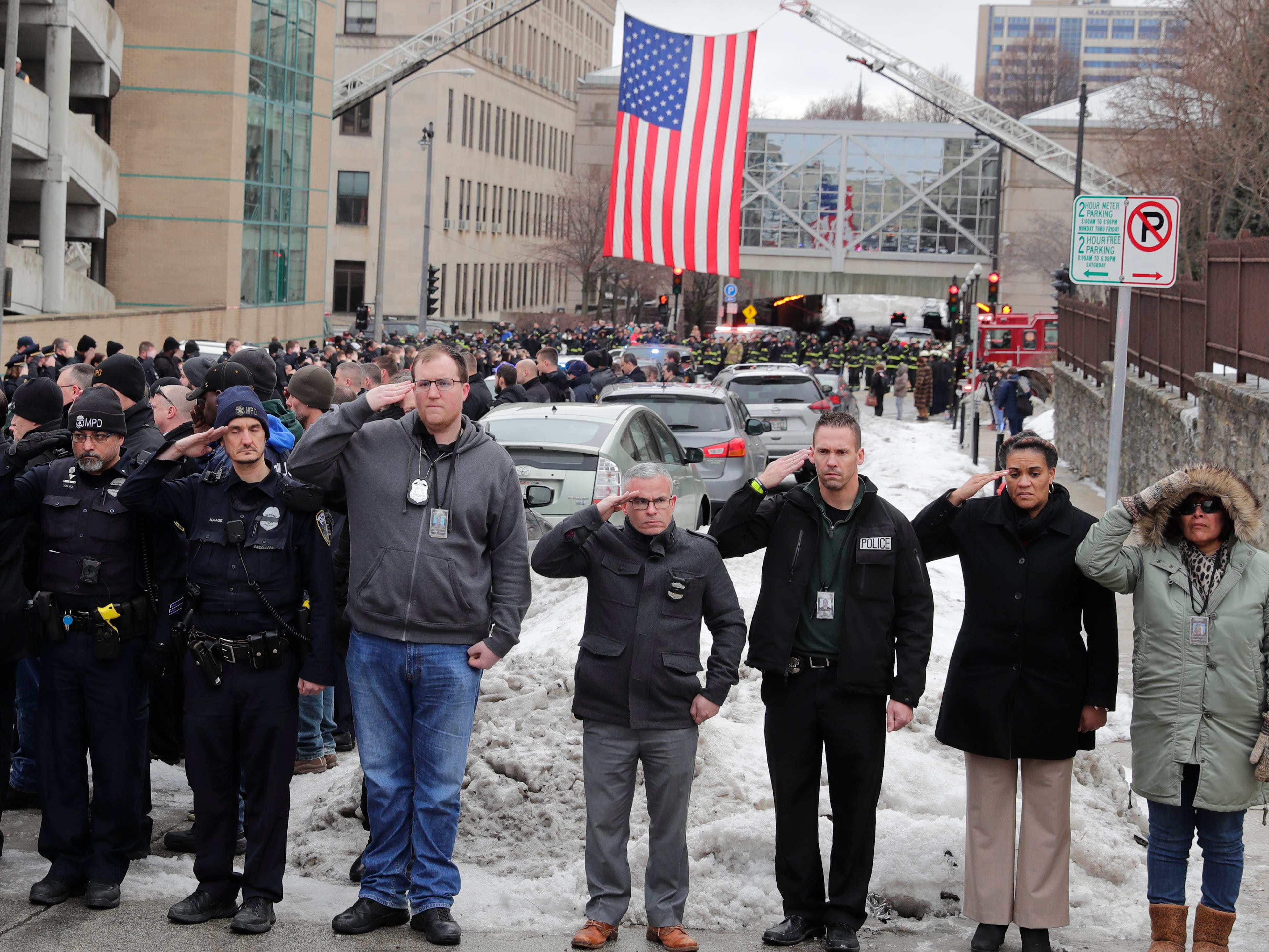 Police officers pay their respects as a procession of police vehicles leads a hearse carrying the body of a fallen Milwaukee officer to the county medical examiner's office Wednesday. The officer was killed Wednesday morning.
