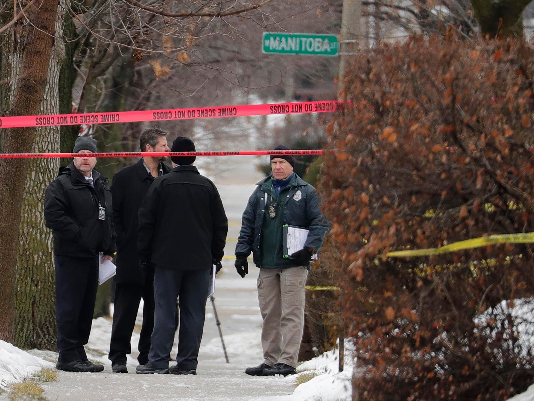 Milwaukee police inspectors gather in front of a home near South 12th and West Dakota streets that was taped off as a crime scene after a Milwaukee police officer was shot Wednesday morning on the city's south side.
