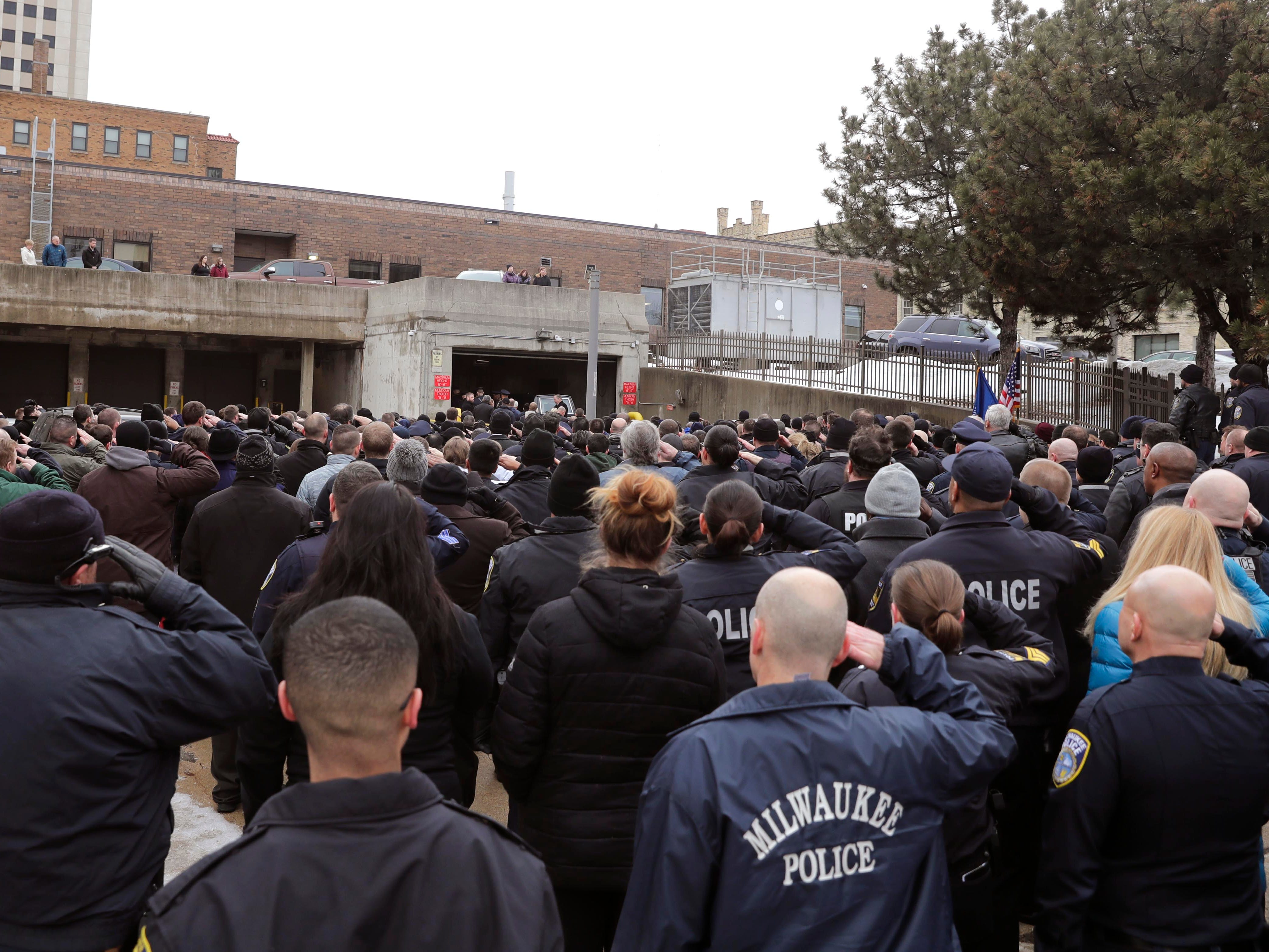 Hundreds of police officers salute their fallen comrade as his body arrived at the Milwaukee County Medical Examiner's Office Wednesday.