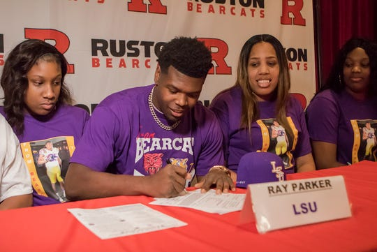 Ray Parker, center, who recently graduated from Ruston High School, signs a National Letter of Intent earlier this year to continue his studies and football career at Louisiana State University.
