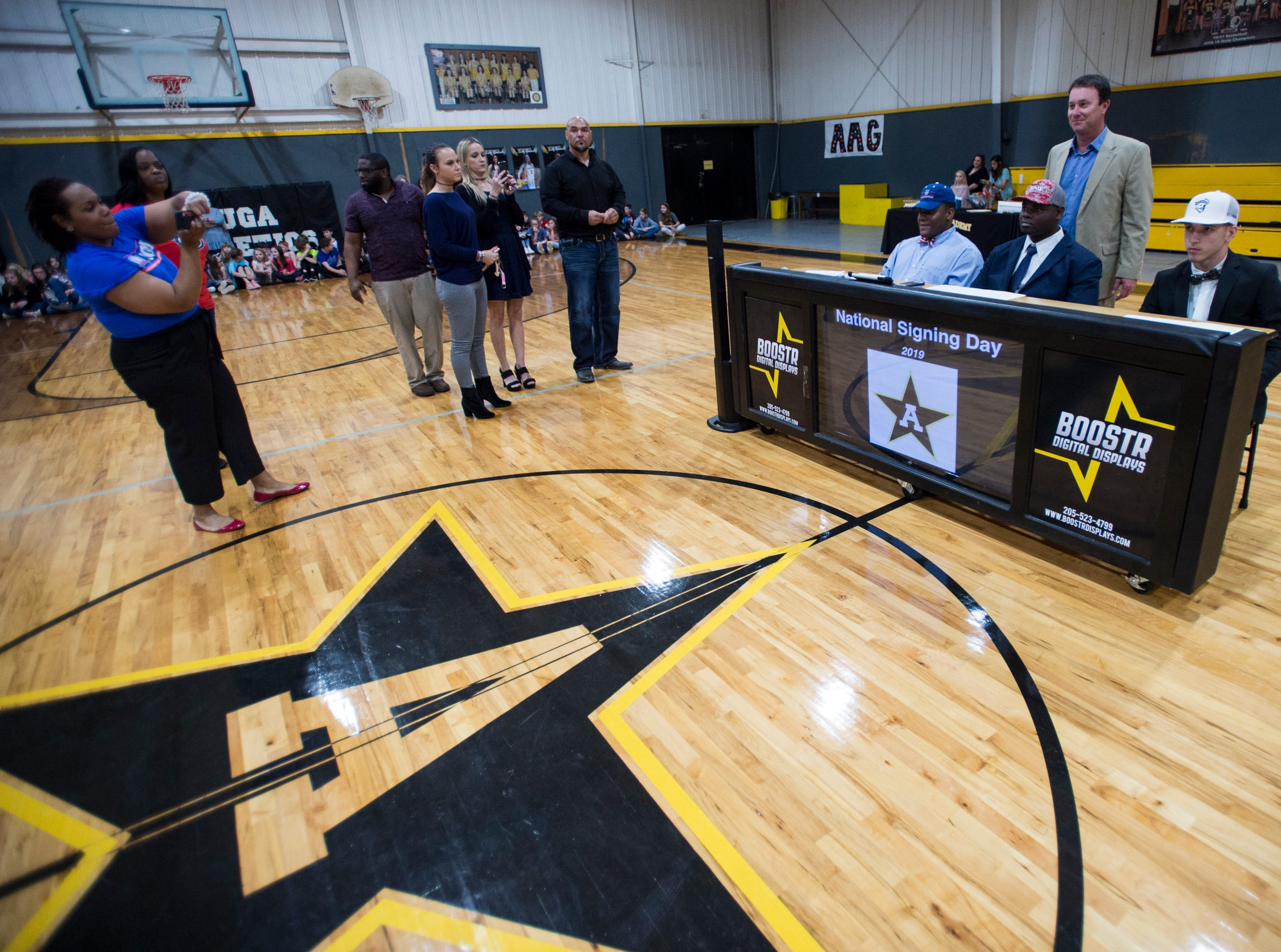 Coach Bobby Carr poses for a picture with his players during signing day at Autauga Academy Prattville, Ala., on Wednesday, Feb. 6, 2019.