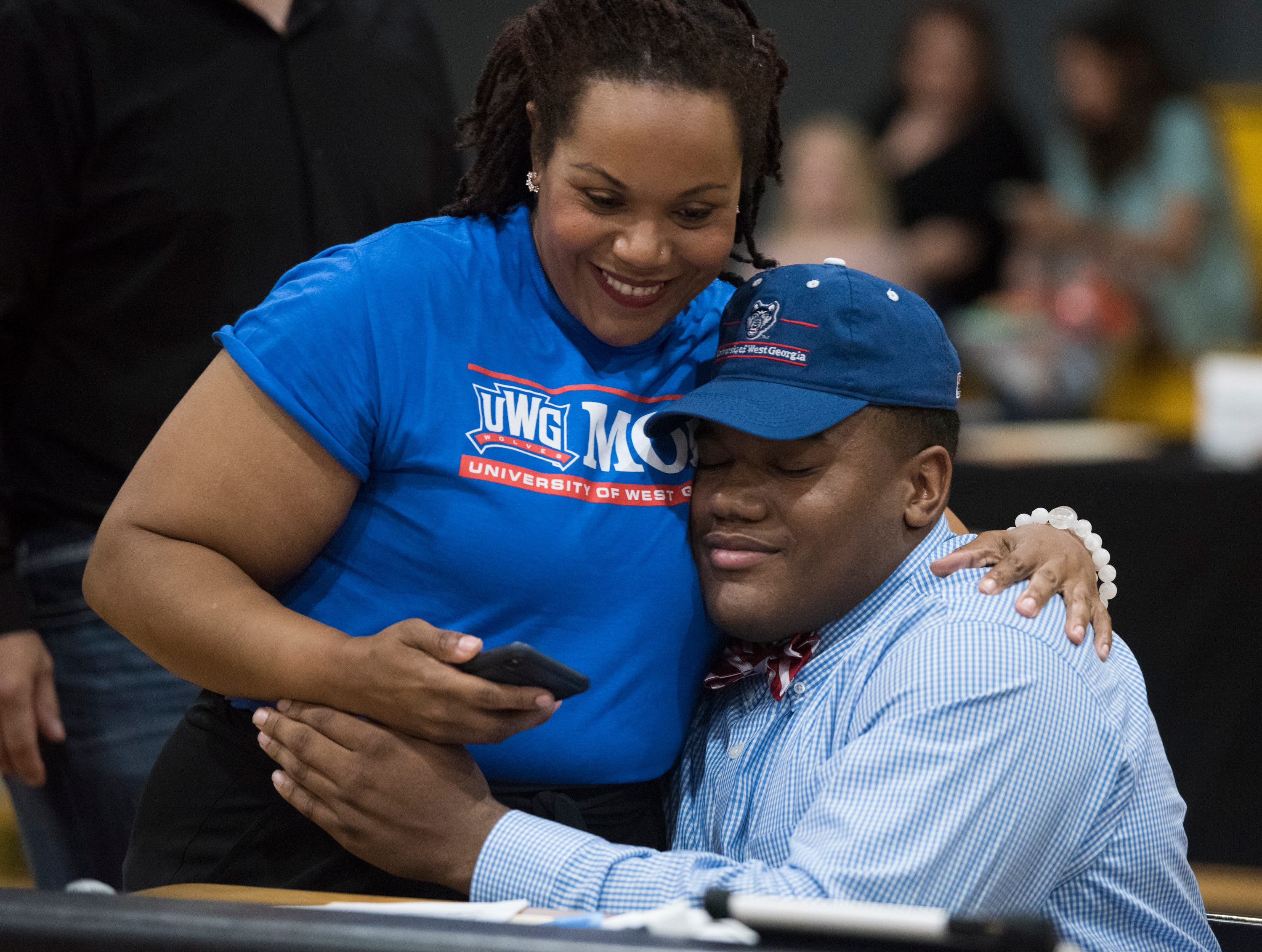 Elijah Elmore hugs his mom after announcing his signing with West Georgia during signing day at Autauga Academy Prattville, Ala., on Wednesday, Feb. 6, 2019.