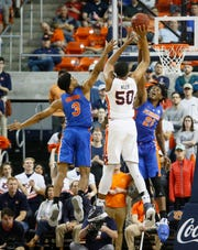 Auburn center Austin Wiley (50) shoots over Florida's Jalen Hudson (3) and Dontay Bassett (21) on Feb. 5, 2019.