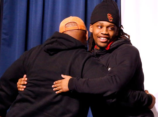 Adonis Otey is congratulated by a supporter after signing a letter of intent to play football at the University of Southern California at Blackman High School on Wednesday, Feb. 6, 2019, on National Signing Day.