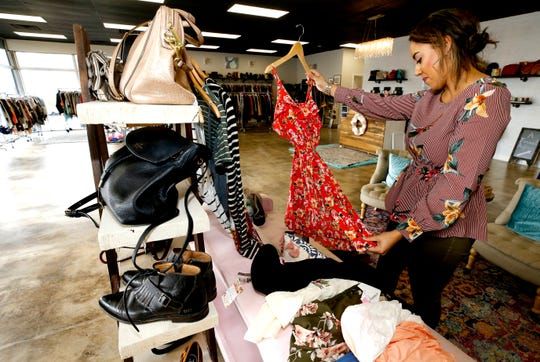 Amelia Dap puts pre-loved items of clothing on hangers Tuesday, Feb. 5, 2019, at The Exchange Boutique off the square in Murfreesboro.