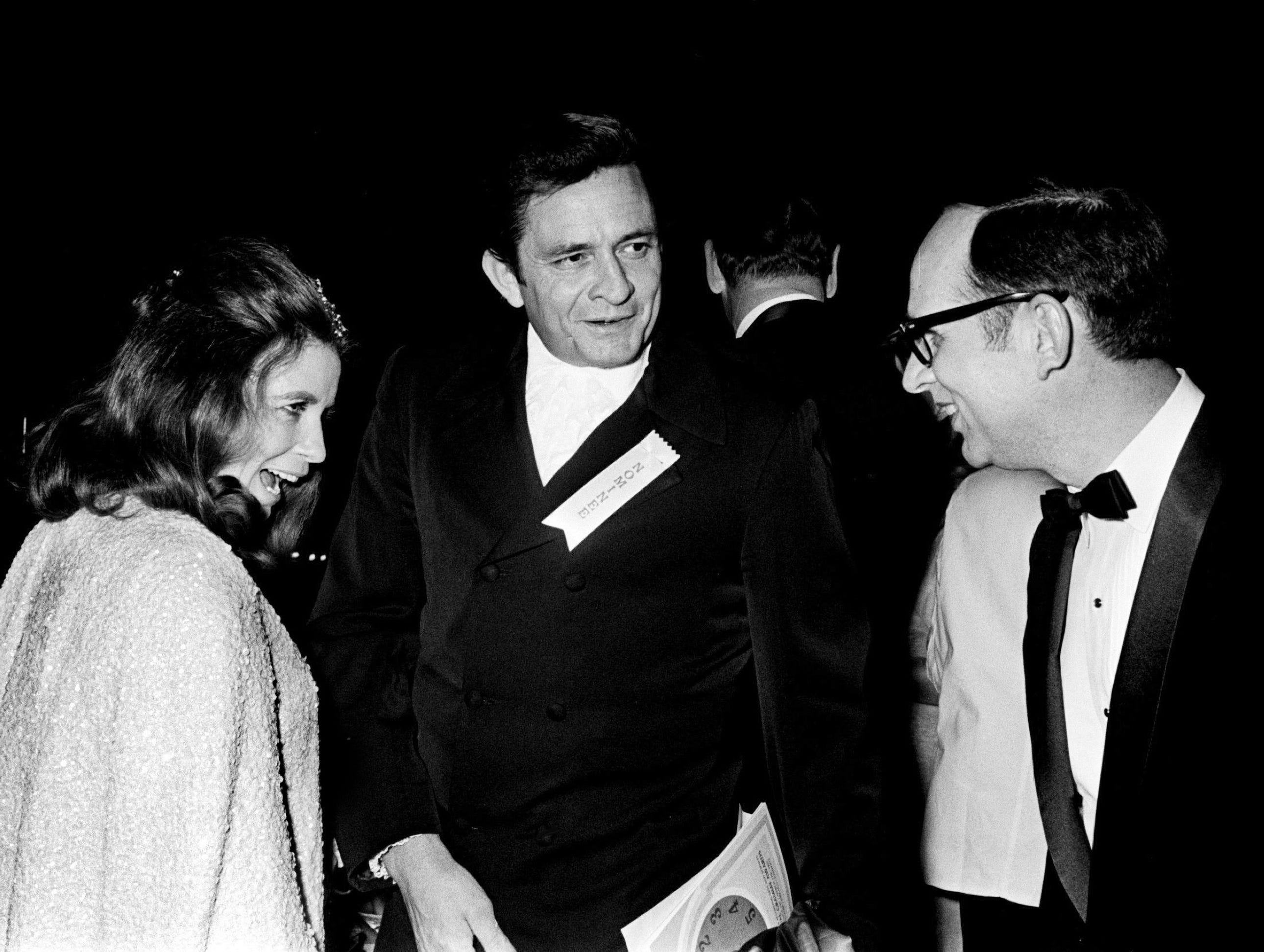 June Carter Cash, left, and Johnny Cash greets a guest after arriving for the 11th annual Grammy Award show at the National Guard Armory in Nashville March 12, 1969. The awards were presented simultaneously at banquets in New York, Chicago, Los Angeles and Nashville.