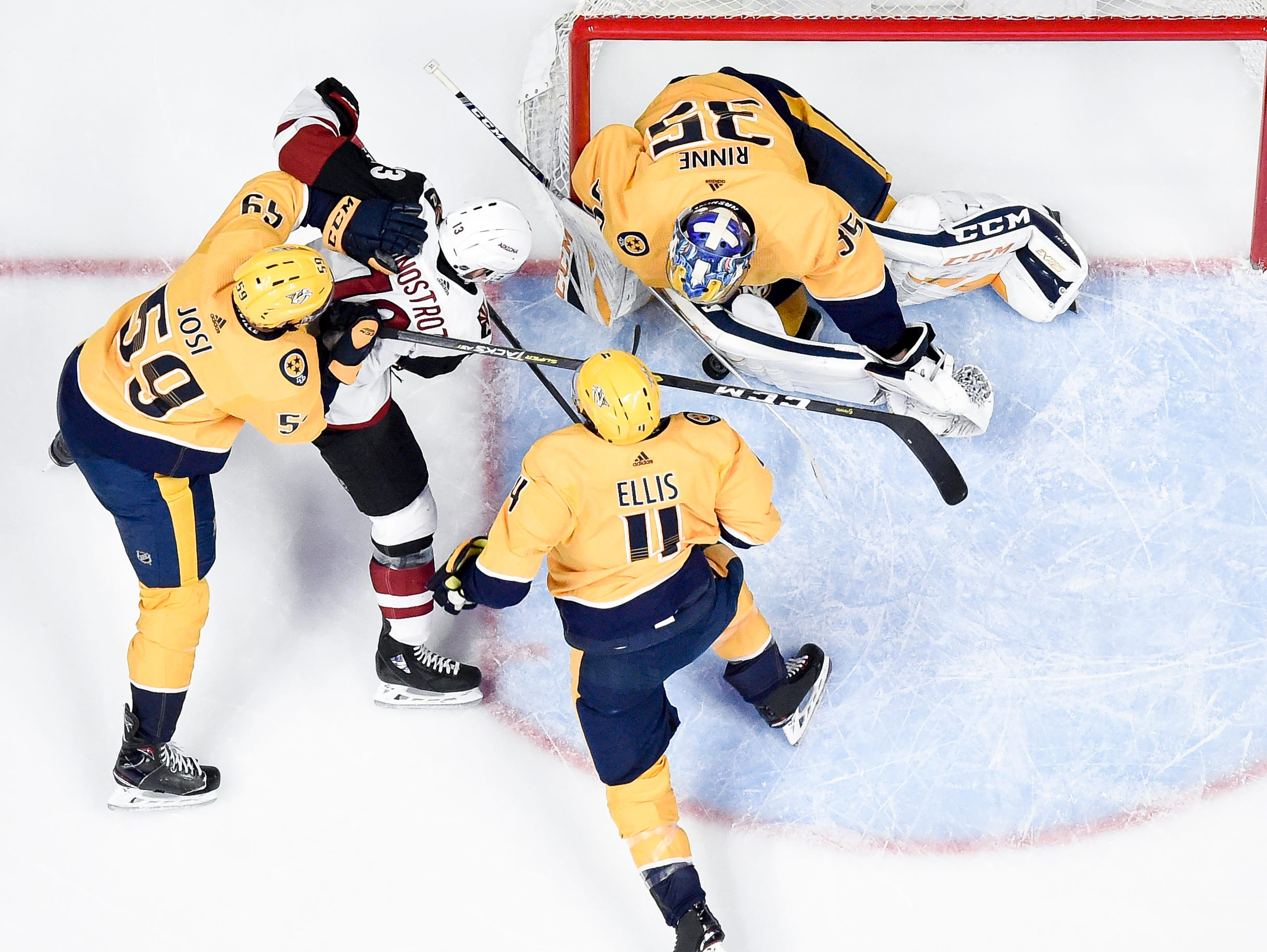 Nashville Predators goaltender Pekka Rinne (35), defenseman Roman Josi (59), and defenseman Mattias Ekholm (14) defend against Arizona Coyotes center Vinnie Hinostroza (13) during the first period at Bridgestone Arena in Nashville, Tenn., Tuesday, Feb. 5, 2019.